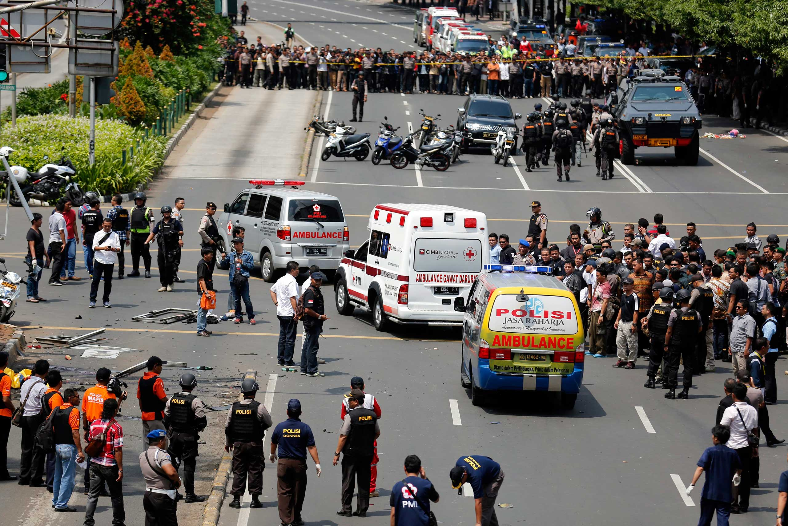 Police ambulances pass the crowds carrying victims to the hospital after a bomb blast in front of a shopping mall in Jakarta, Indonesia, Jan. 14, 2016.