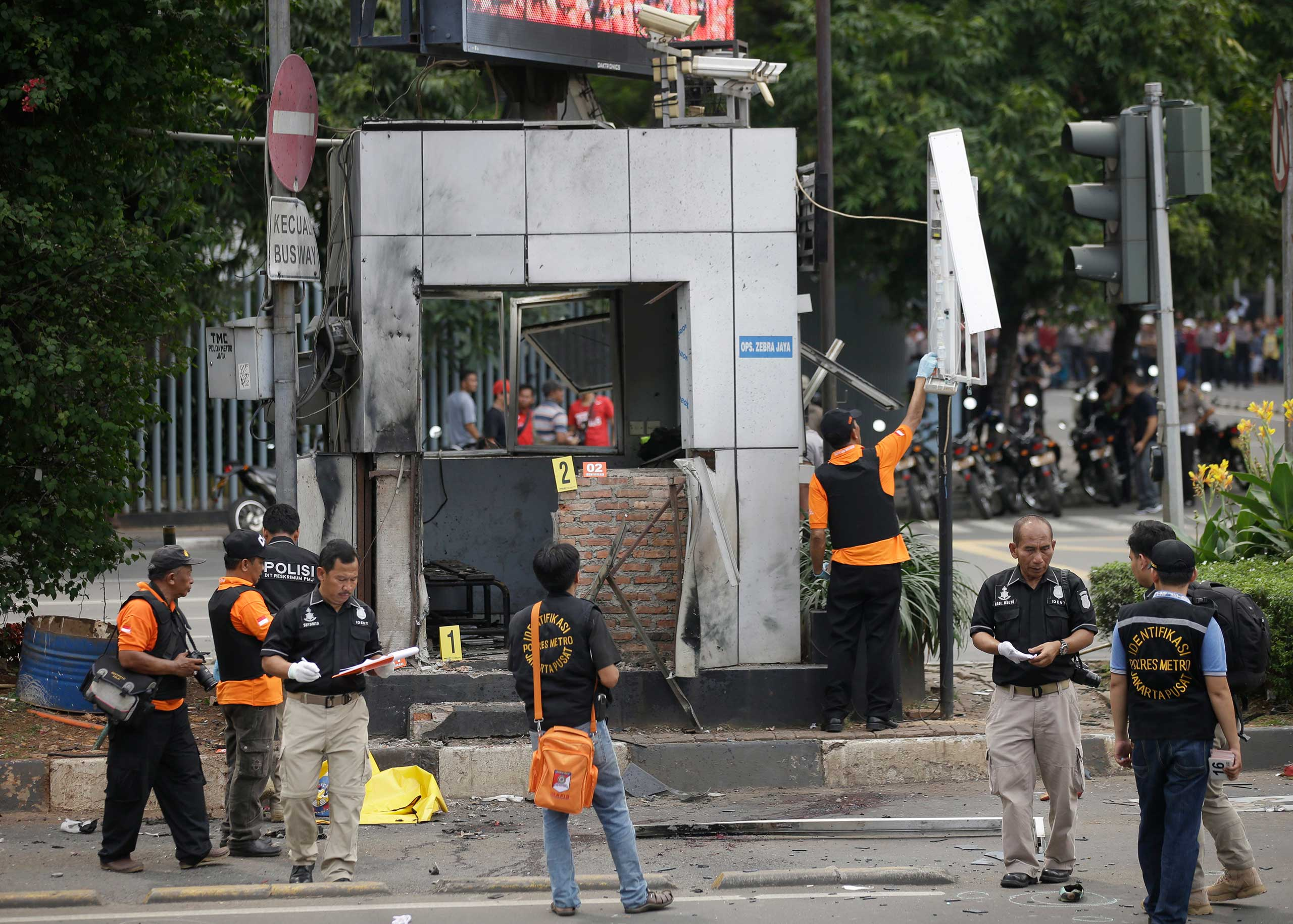 Officers examine a police post where an explosion went off in Jakarta, Indonesia, Jan. 14, 2016. Attackers set off explosions in a bustling shopping area in Indonesia's capital and waged gun battles with police, leaving bodies in the streets as office workers watched from high-rise windows.