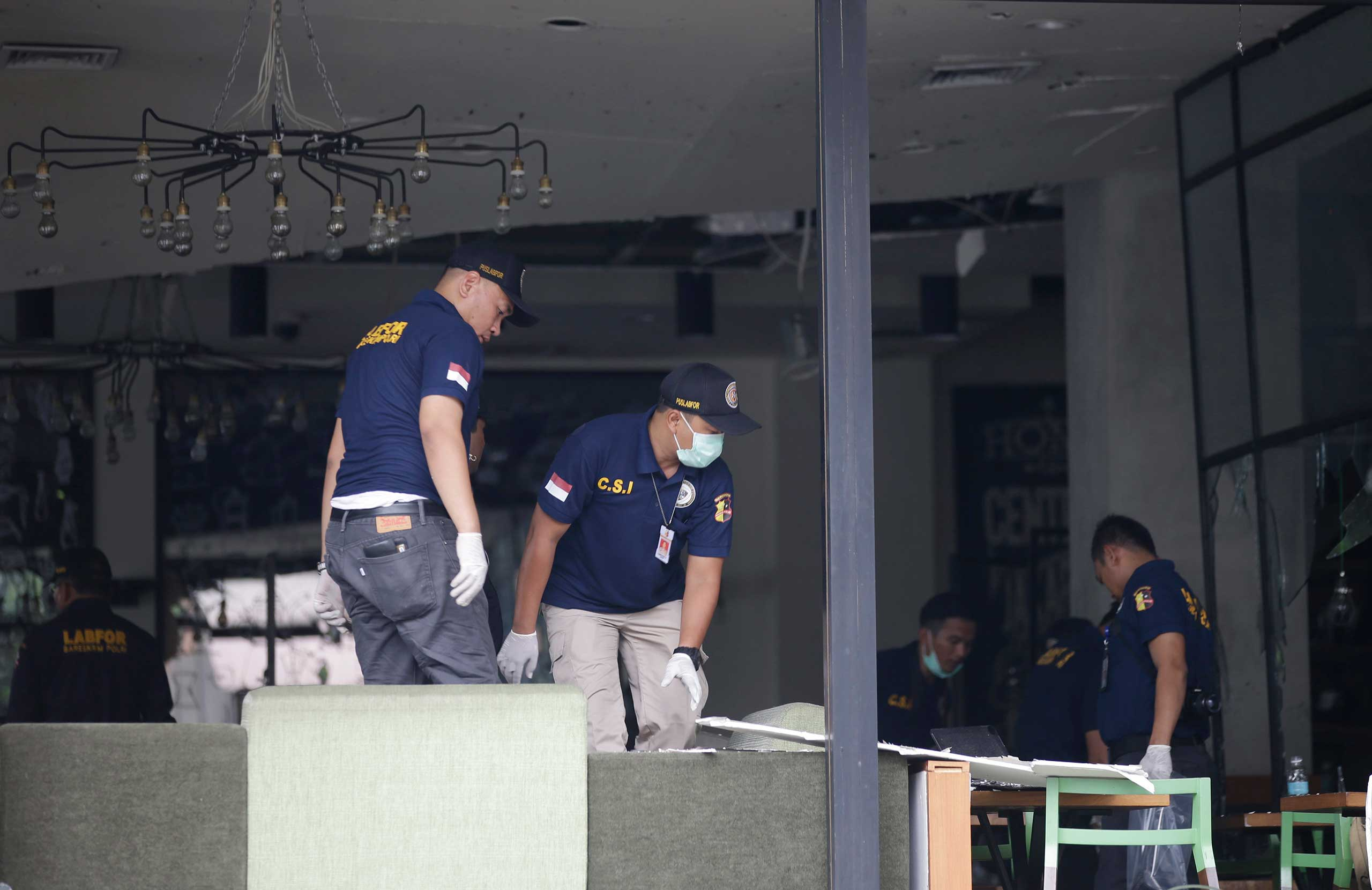 Police officers examine a damaged Starbucks café after an attack in Jakarta, Indonesia, Jan. 14, 2016.
