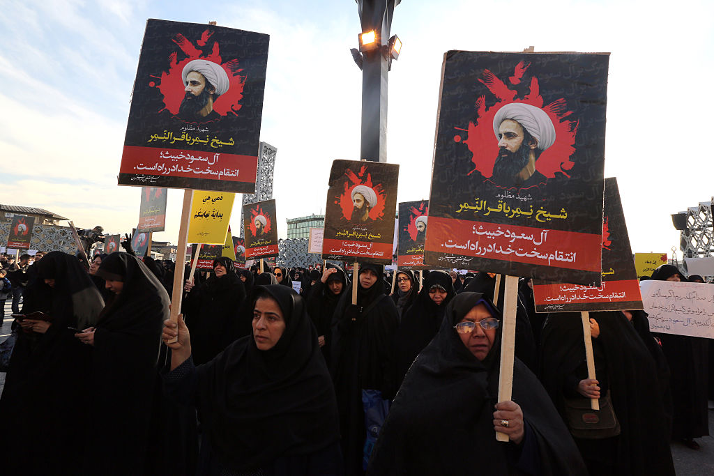 Iranian women gather during a demonstration against the execution of prominent Shiite Muslim cleric Nimr al-Nimr (portrait) by Saudi authorities, at Imam Hossein Square in the capital Tehran on Jan. 4, 2016.