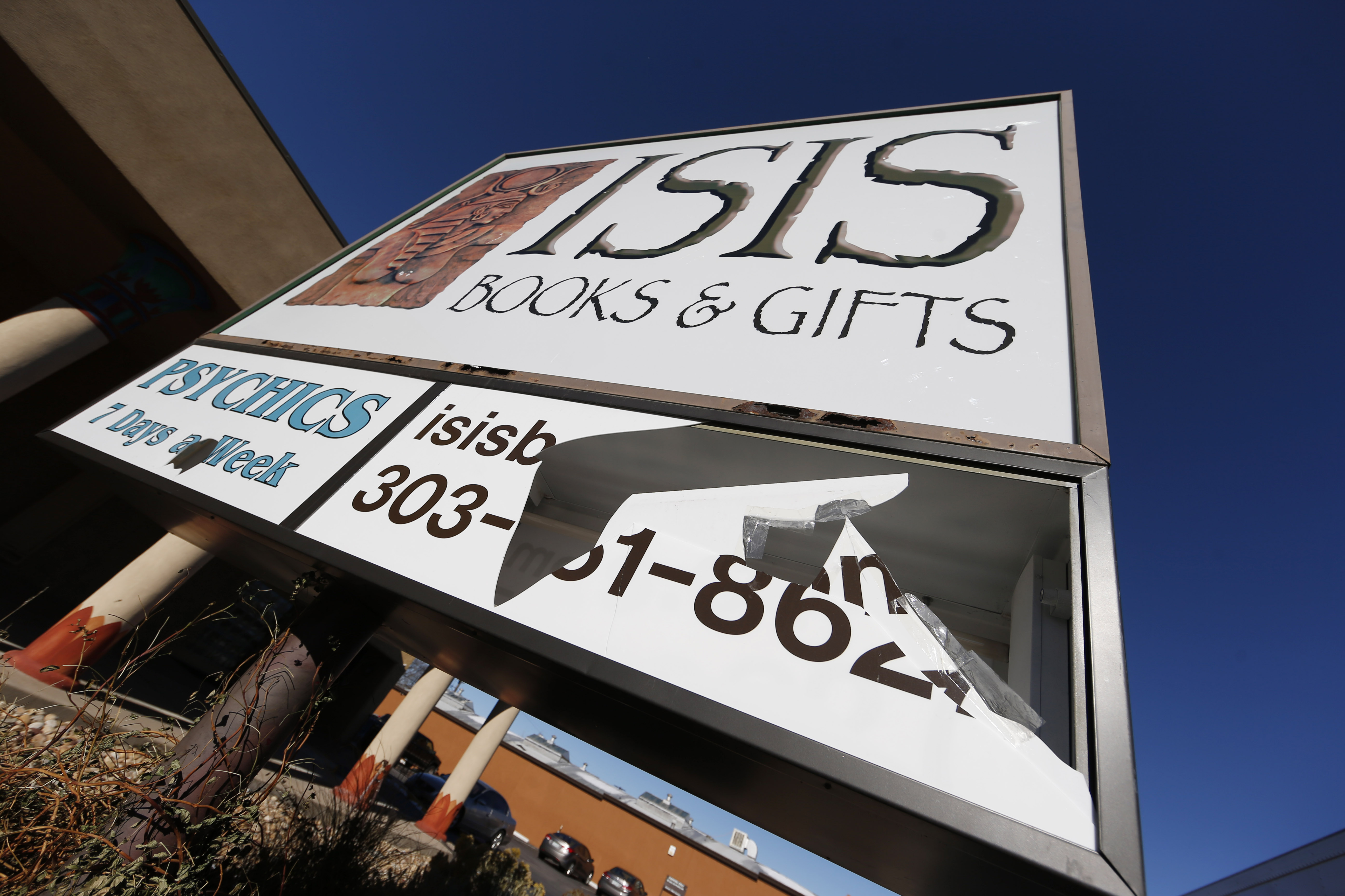 A panel of the sign outside Isis Books and Gifts is shown broken on Nov. 18, 2015, in Englewood, Colo.