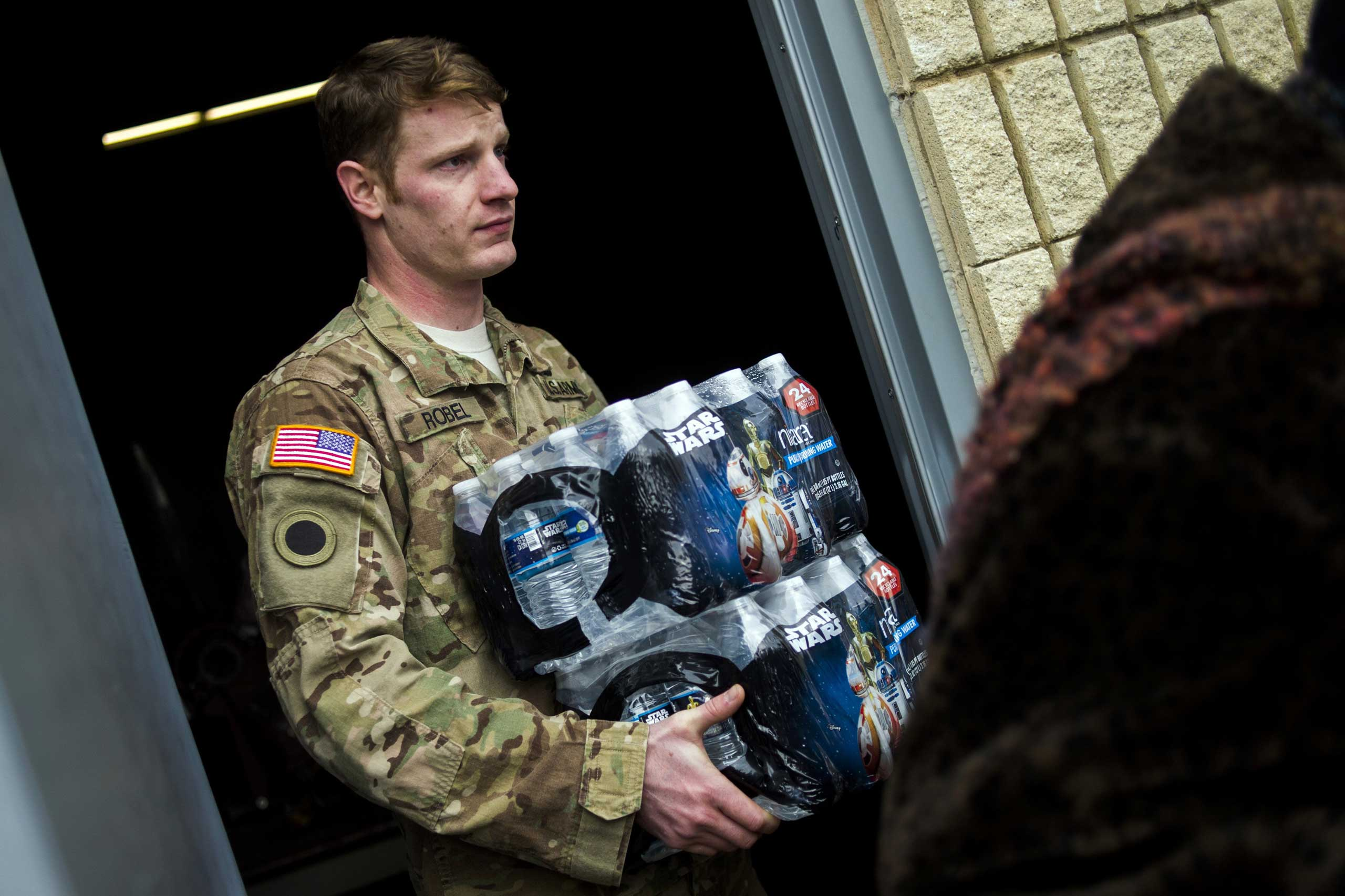 Michigan National Guard Staff Sgt. Stephen Robel helps carry a case of water to the vehicle of Flint resident Karand Houston as the first seven Michigan National Guard soldiers arrive on the ground at fire stations on Jan. 13, 2015 throughout Flint. They were assigned by Gov. Rick Snyder on Tuesday to help distribute water and relieve residents in relation to the Flint water crisis. Safe drinking water has not flowed from many Flint faucets for almost two years, after the state-run city switched its source to the highly corrosive Flint River and failed to treat it properly to protect lead from leaching into it.