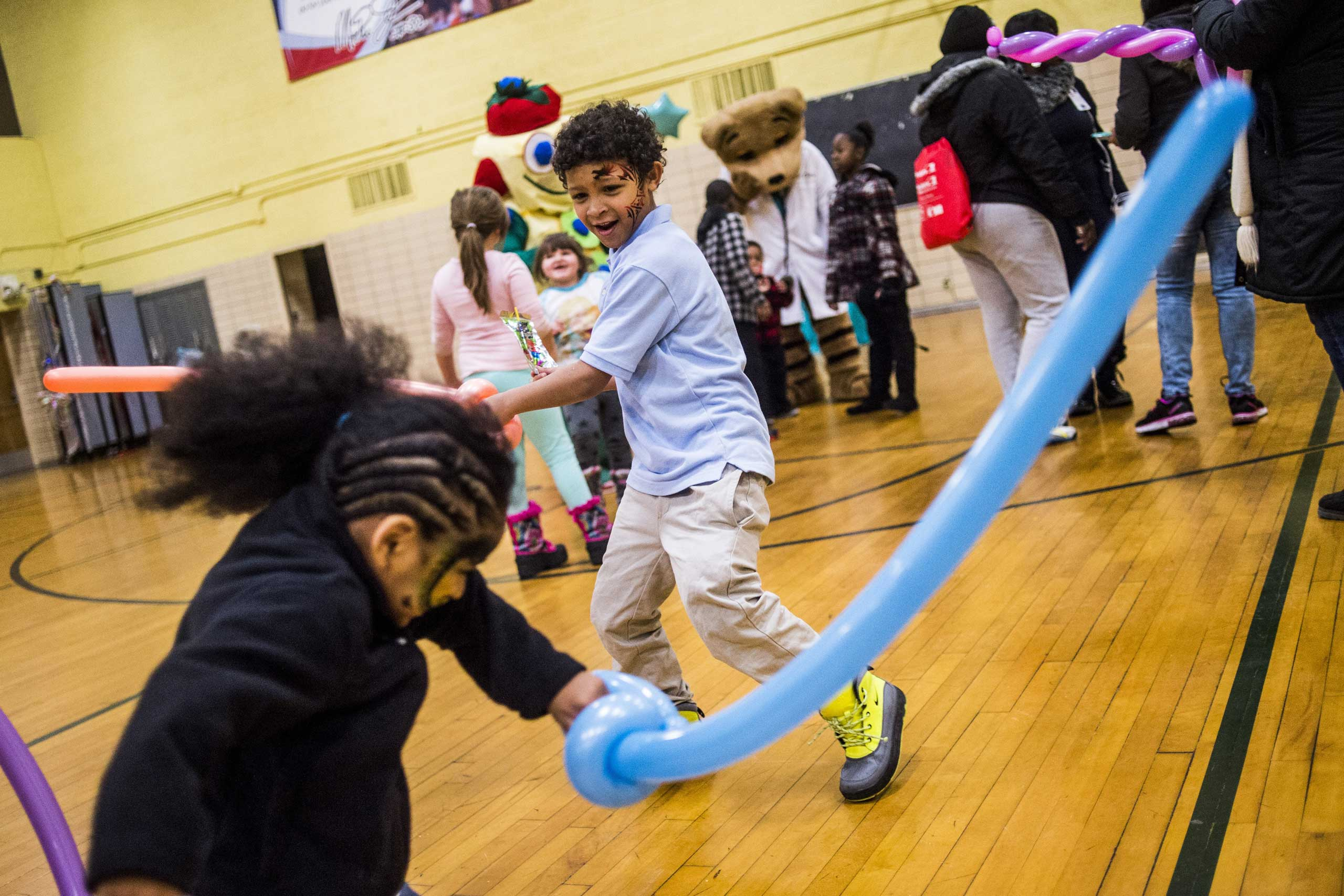 Freeman Elementary second-grader Damari Morales, 7, fights with balloon swords with Apollo Williams, 3, both of Flint. The Flint Community Schools, the Genesee County Health Department and Molina Healthcare held a family fun night to get children  tested for lead levels in their blood at the school in Flint, Mich., Jan. 12, 2016.