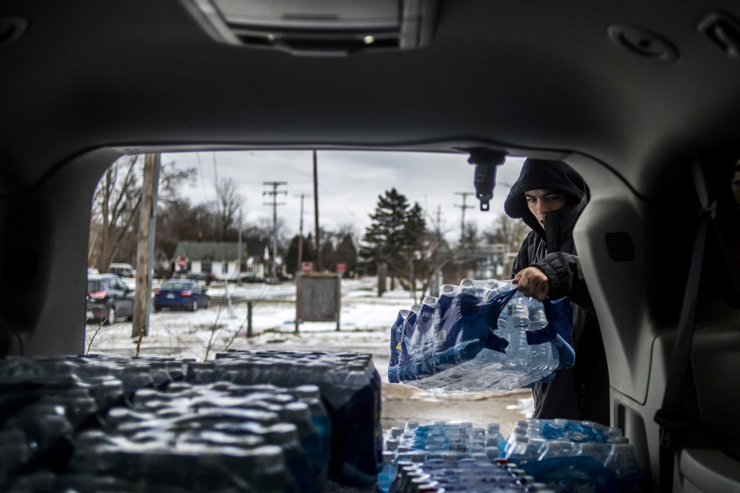 Flint resident Randy Huyck Jr., 17, throws a case of bottled water into the back of a volunteer's car as Detroit-area volunteers drop off more than 500 cases of bottled water in Flint, Mich. on Jan. 16, 2016.
