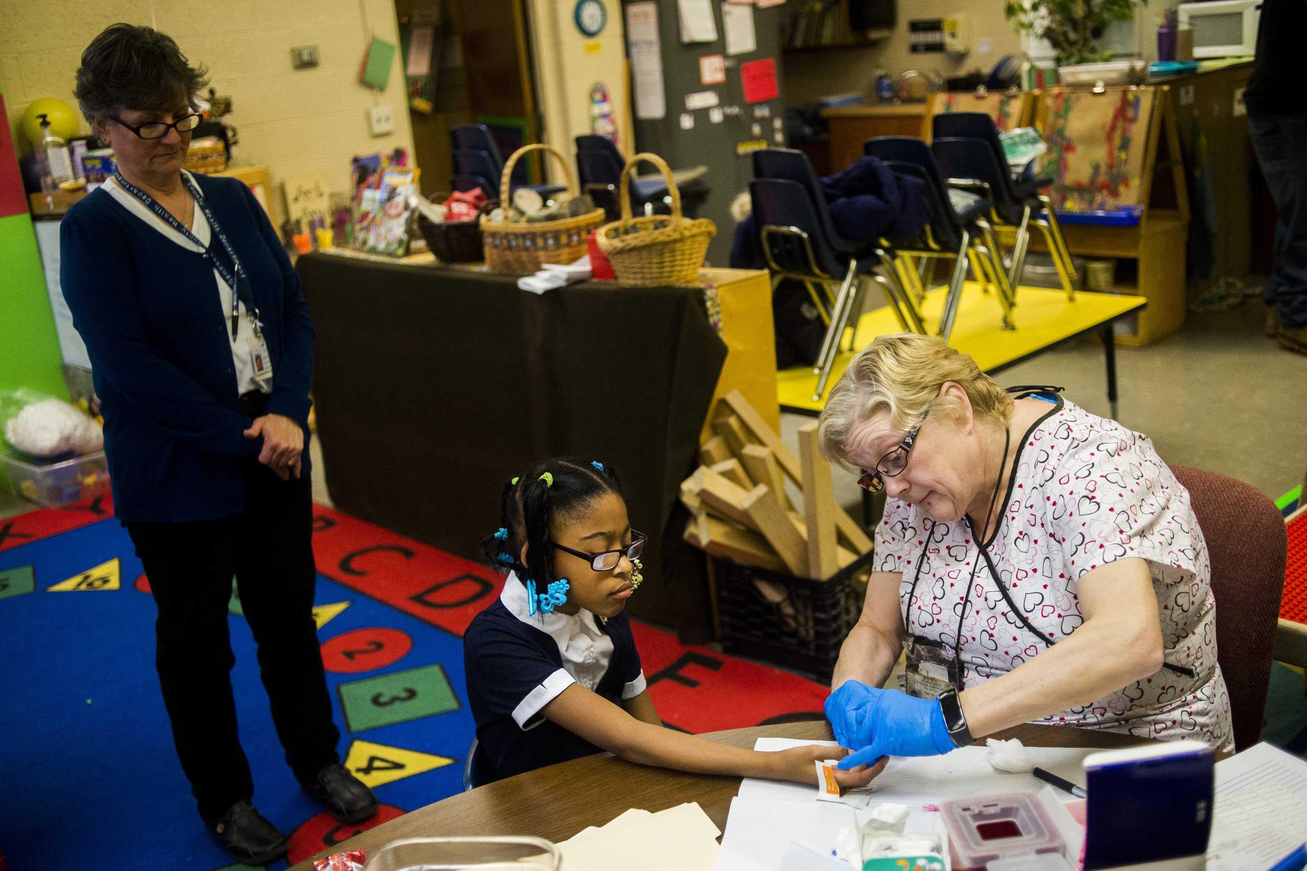 LaShanti Redmond, 10, of Flint, gets her finger poked to test her blood for lead levels at Freeman Elementary School in Flint, Mich., Jan. 12, 2016.