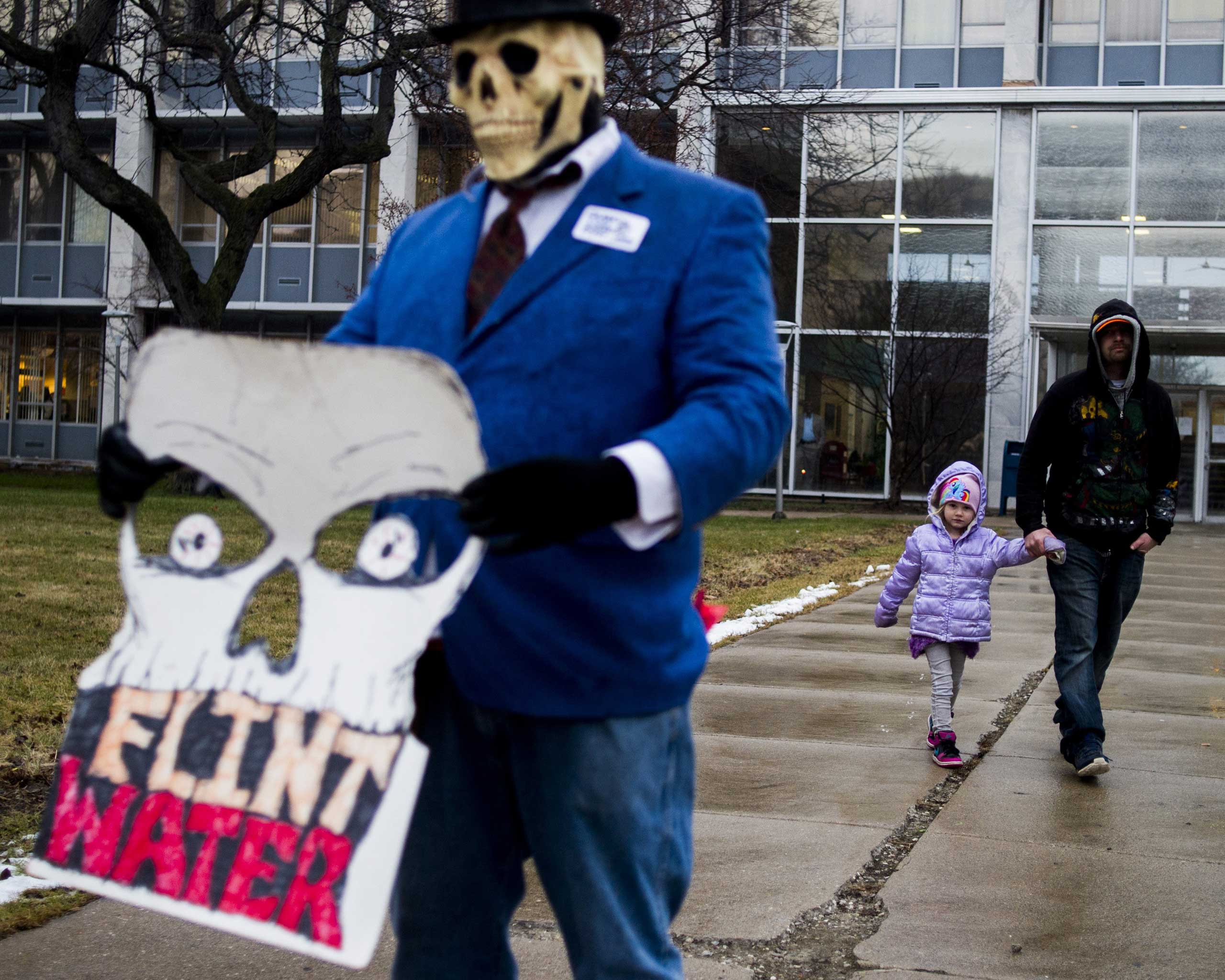 Flint resident Mike Hickey holds the hand of his daughter Natielee, 4, as they walk past activists who are outside of City Hall to protest Michigan Gov. Rick Snyder's handling of the water crisis Jan. 8, 2016 in Flint. Mich.