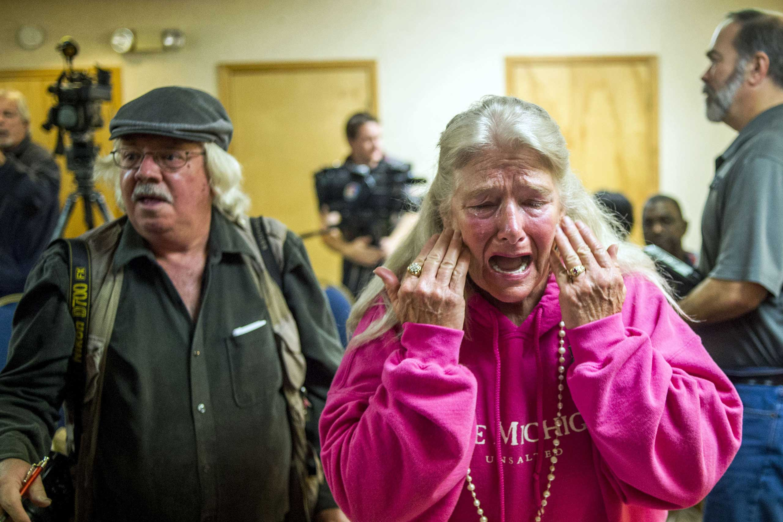 Flint resident Gladyes Williamson cries out through her tears to Melissa Mays, one of six plaintiffs, overwhelmed with frustration of the water issue and joy in the filing of a potential class action lawsuit against both city and state government officials on Nov. 16, 2015, at the Holiday Inn Express in Flint, Mich. The lawsuit claims that these government officials violated constitutional rights by providing lead-tainted water to residents, which led to alleged developing health issues, including hair loss, depression and auto-immune disorders.
