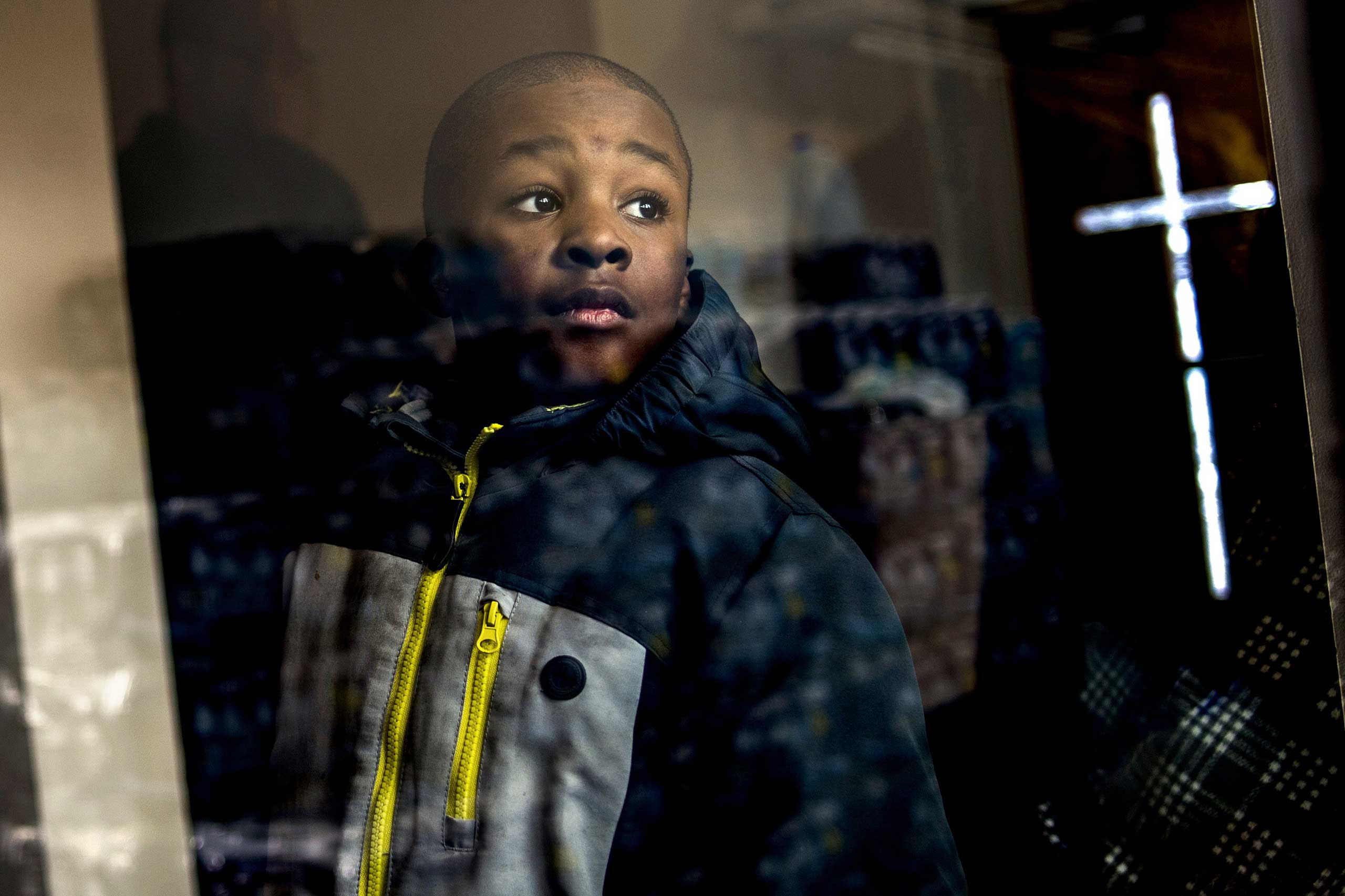 Detroit resident Jaiden Ellis, 8, looks at stacks of free bottled water to be given to the congregation while the Rev. Jesse Jackson, a civil rights leader, discusses the ongoing Flint water crisis on Jan. 17, 2016, in Flint, Mich.