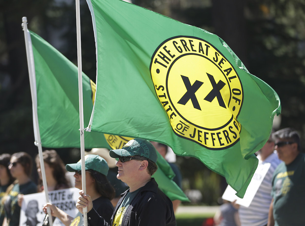 With flags showing the double XX,  representing the state of Jefferson, fluttering in the breeze, dozens of residents from several rural counties rallied at the Capitol on Aug. 28, 2014, in Sacramento, Calif.