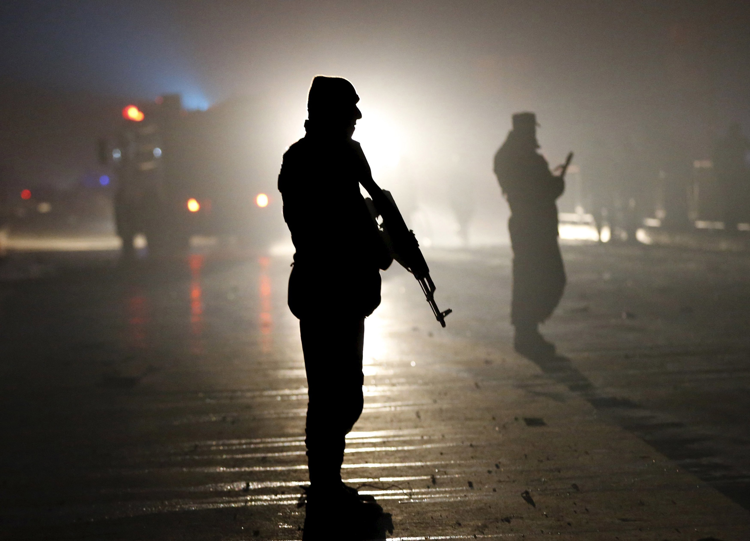 Afghan policemen stand guard at the site of a suicide bomb attack in an area near the Russian embassy in Kabul, on Jan. 20, 2016.