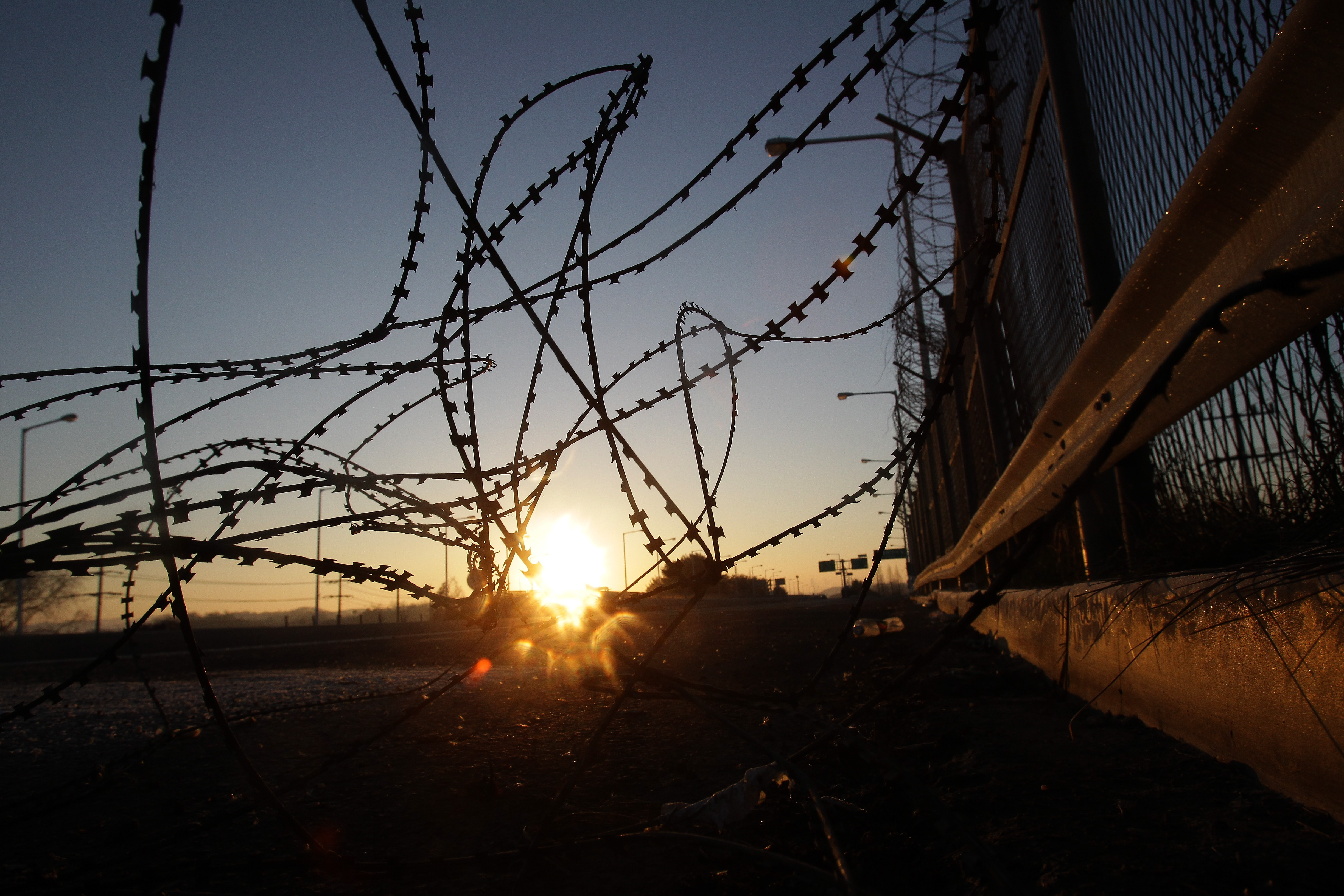 A sunrise is seen through a barbed-wire fence at the Imjingak, near the Demilitarized zone separating South and North Korea in Paju, South Korea, on Jan. 8, 2016.