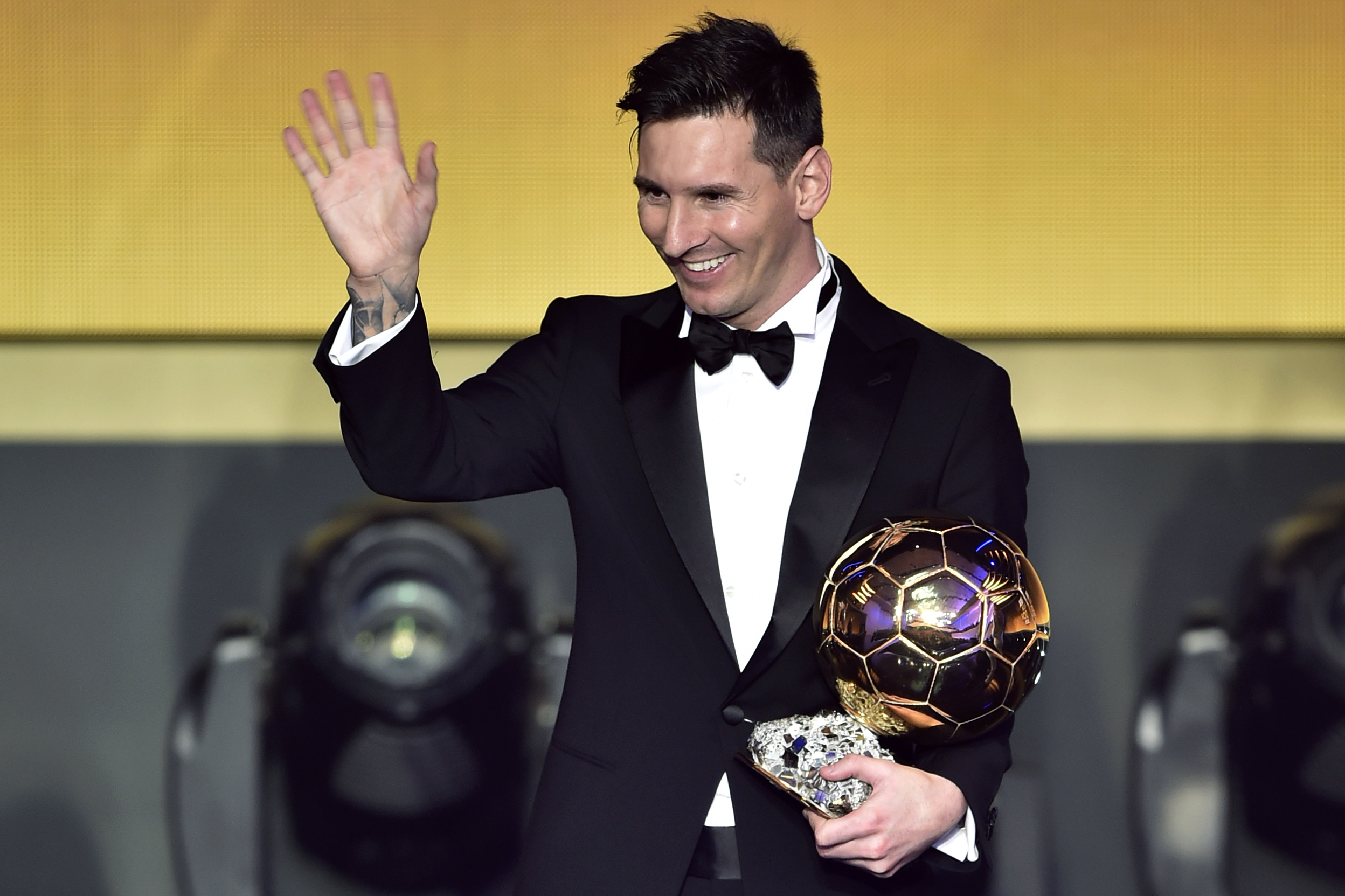 Lionel Messi waves holding his trophy after receiving the 2015 FIFA Ballon dOr award for player of the year during the 2015 FIFA Ballon d'Or award ceremony in Zurich on Jan. 11, 2016.
