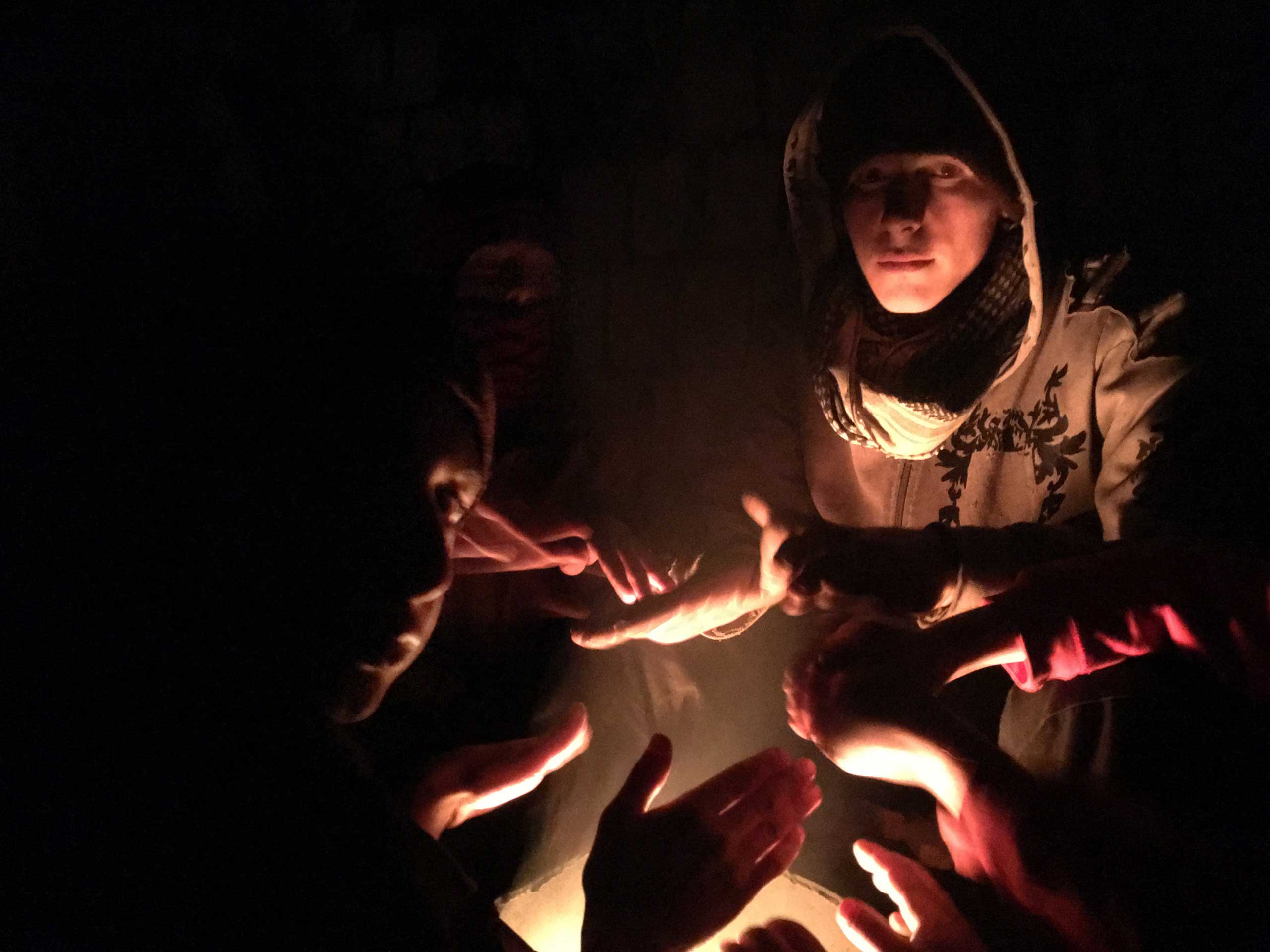 Young people warm themselves over burning garbage before aid is distributed in Madaya, Syria, Jan. 11, 2016.