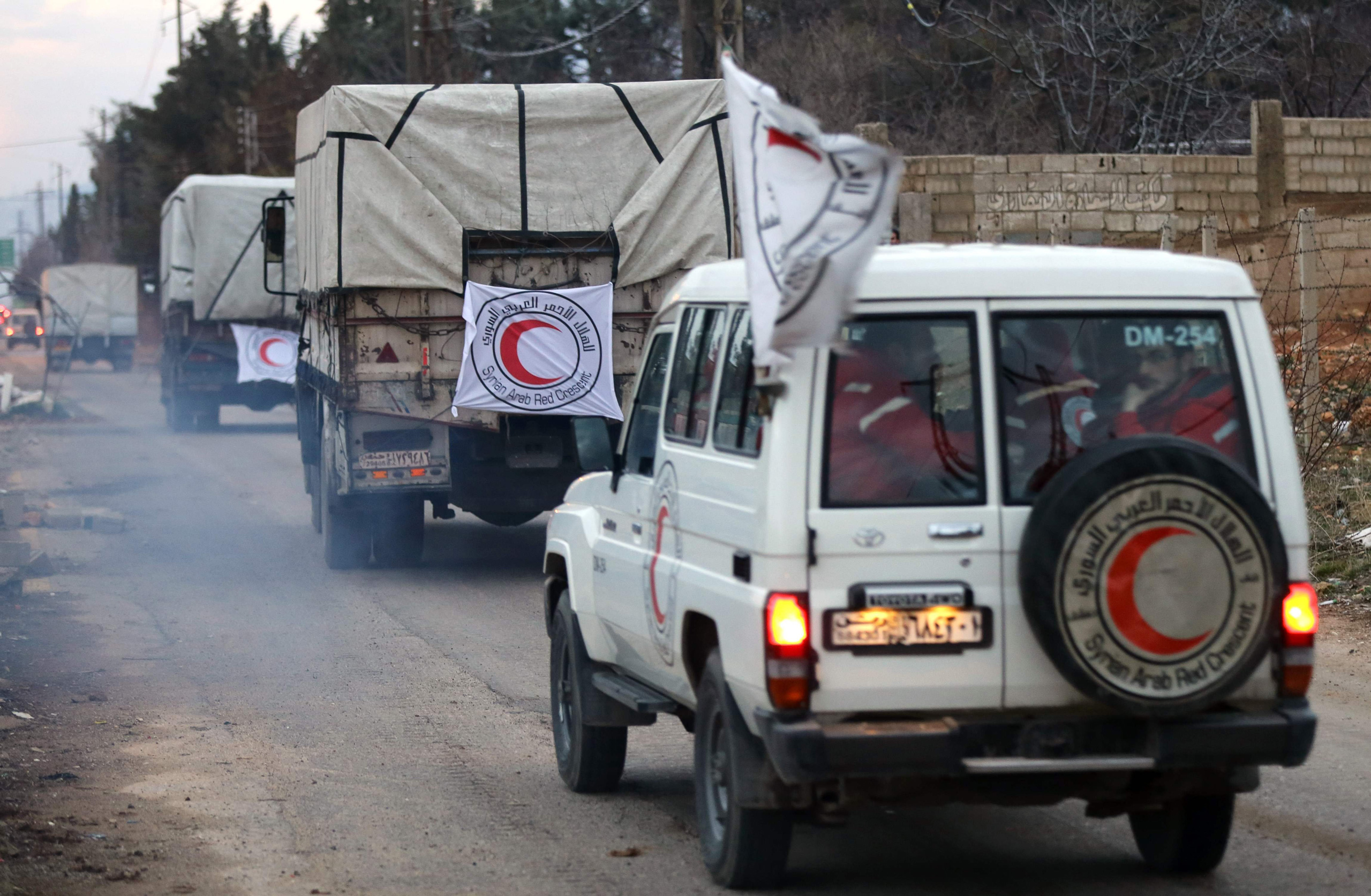 Vehicles from the Syrian Arab Red Crescent drive in a convoy on the outskirts of the besieged rebel-held town of Madaya, Syria, on Jan. 11, 2016.