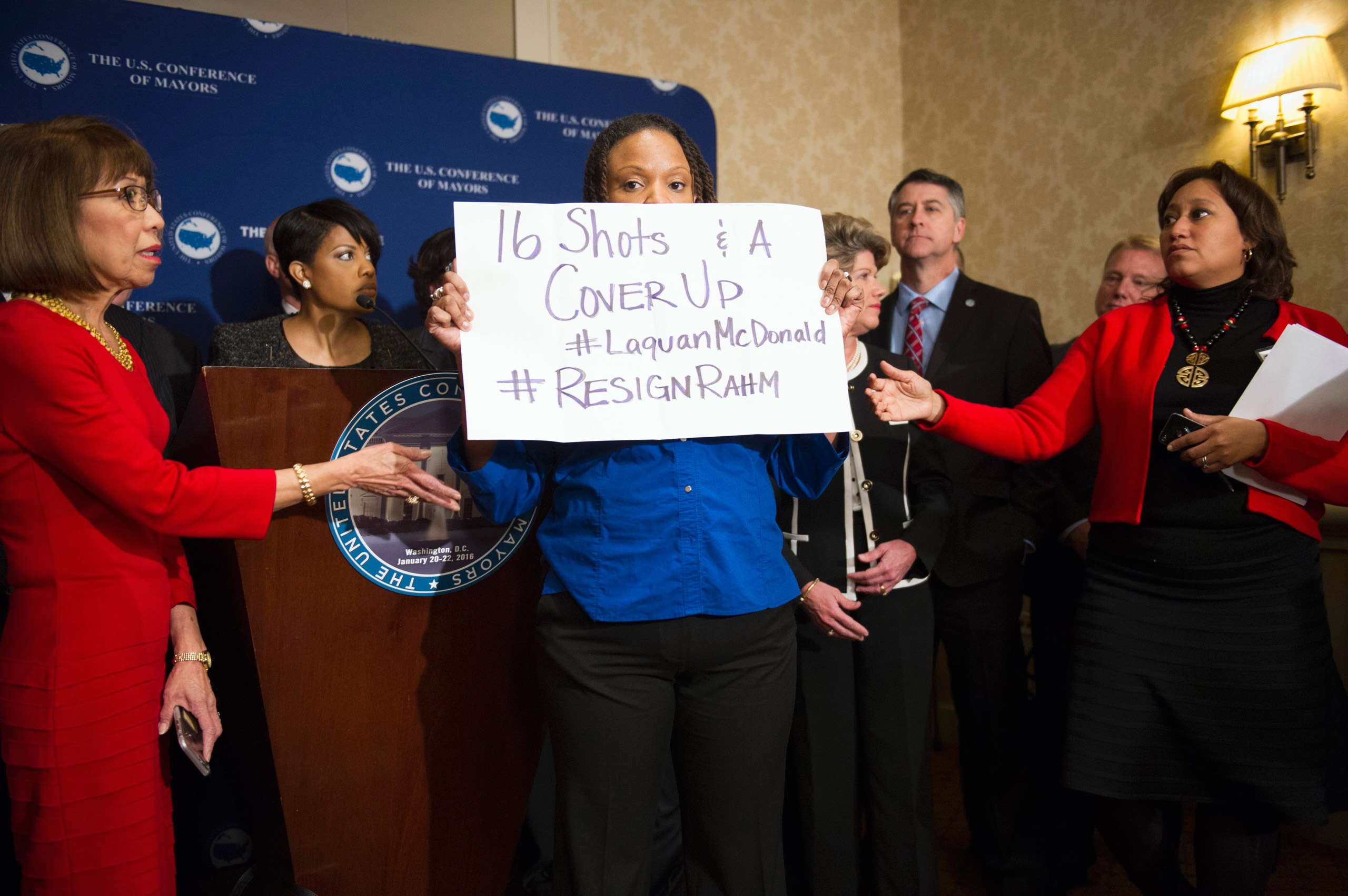 Burnsville, Minn., Mayor Elizabeth Kautz, left, tries to move Black Lives Matters demonstrator April Goggans as she interrupts a news conference during the U..S. Conference of Mayors Winter Meeting in Washington on Jan. 20, 2016.
