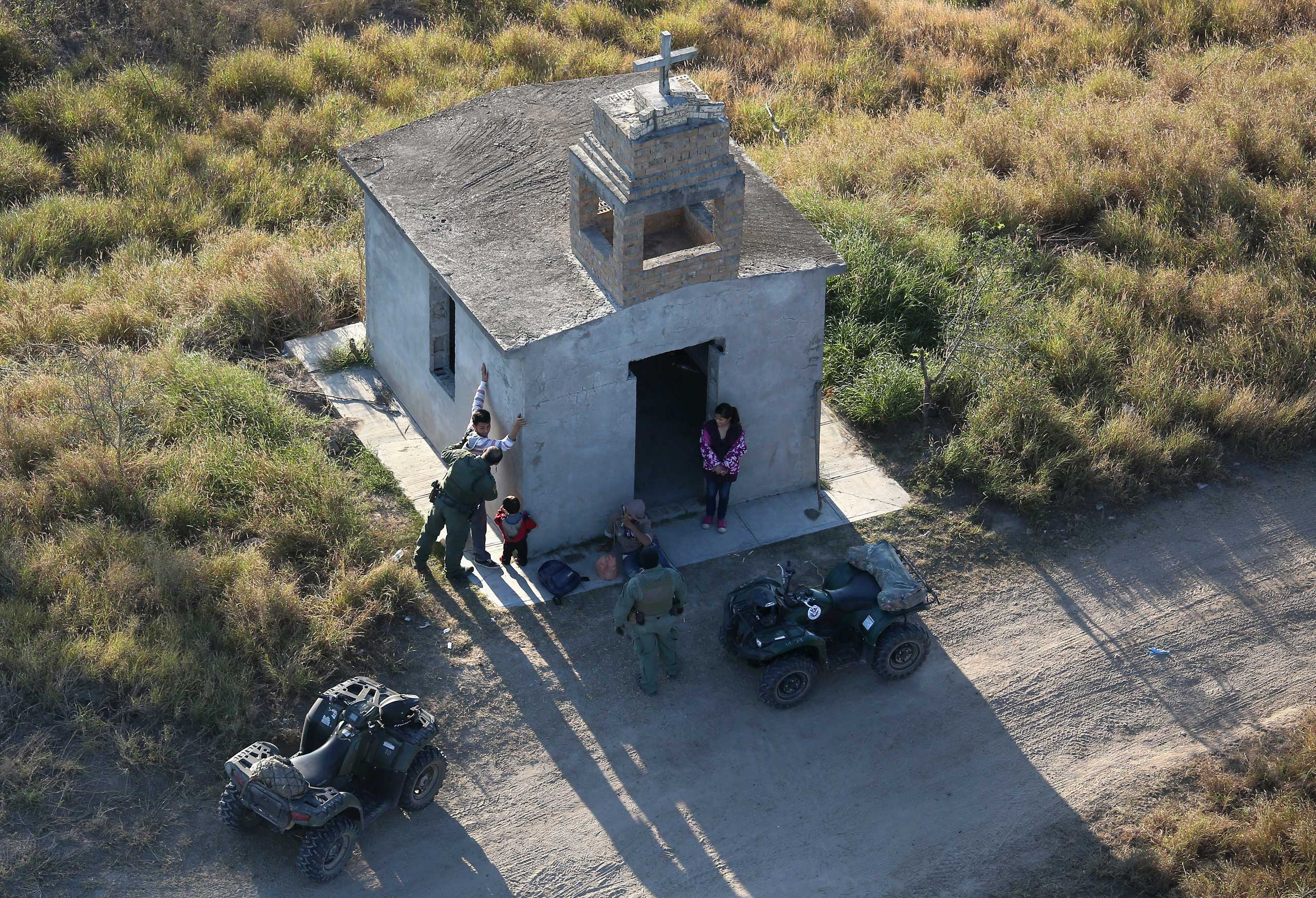 U.S. Border Patrol agents search a migrant family after they crossed the U.S.-Mexico border near Rio Grande City, Texas, on Dec. 9, 2015.