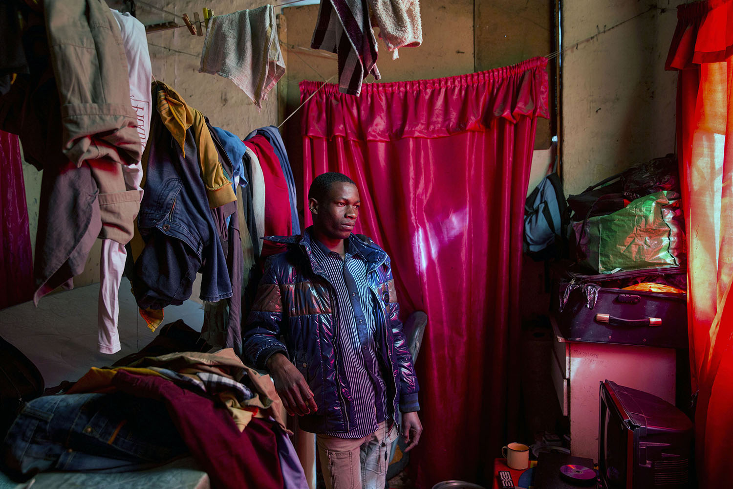 Edward (20 years), a carpenter from Malawi in his small room he shares with four other migrants, July 12, 2015.
