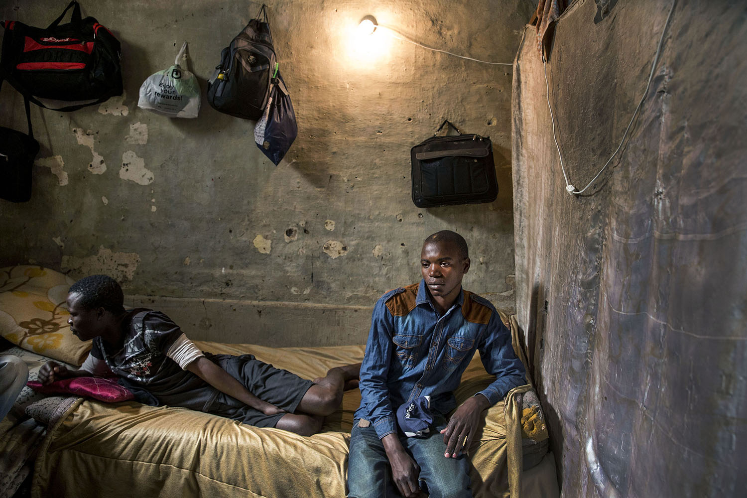 Adam (25 years) from Zambia in a windowless room he shares with four other migrant workers, May 22, 2015.