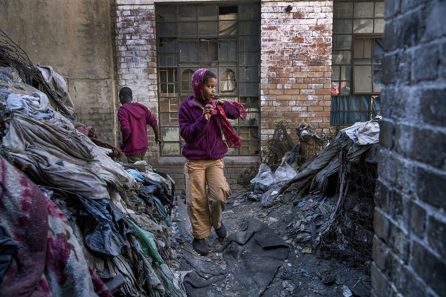 A young girl walks in a rubbish-filled courtyard, July 19, 2015.