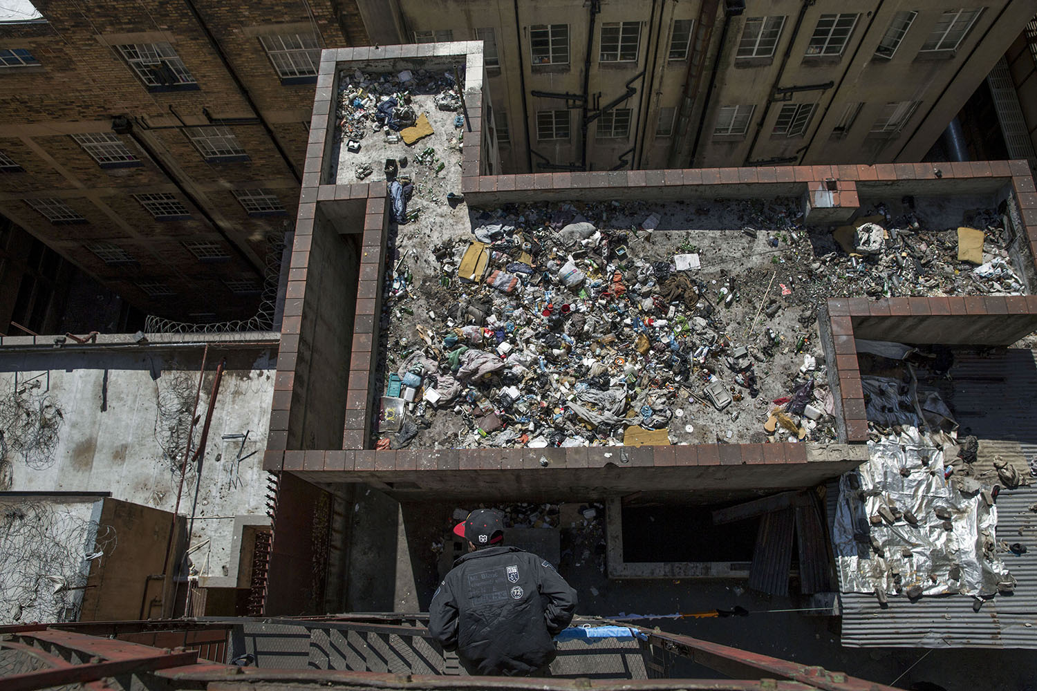 A man looks on to the rubbish filled roof of a derelict building, in the inner city of Johannesburg, Aug. 2, 2015.