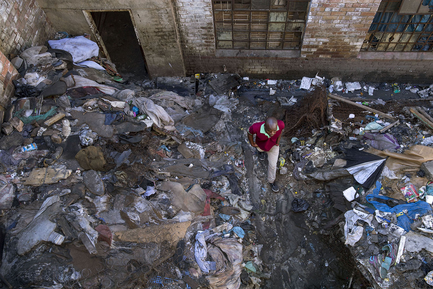 An African migrant resident walking in the rubbish-filled courtyard between two derelict buildings,  July 19, 2015.