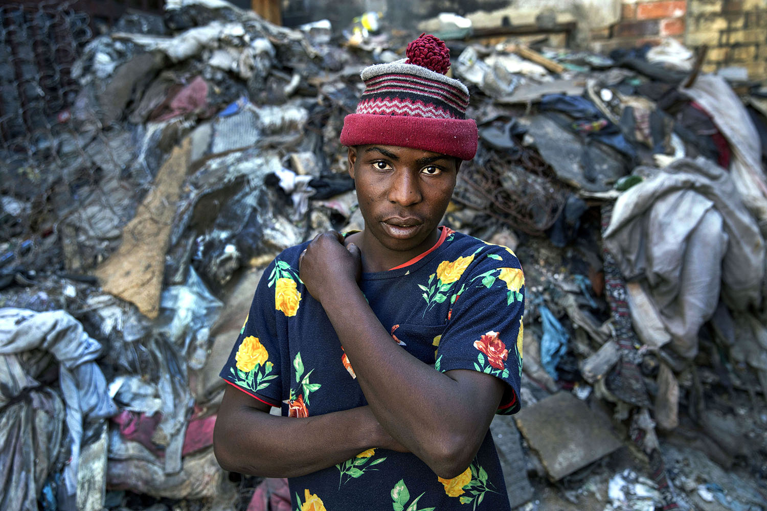 Pumulelo (age 25 ) a migrant from Zimbabwe stands in the piles of rubbish at a derelict building he has made his home, July 19, 2015.