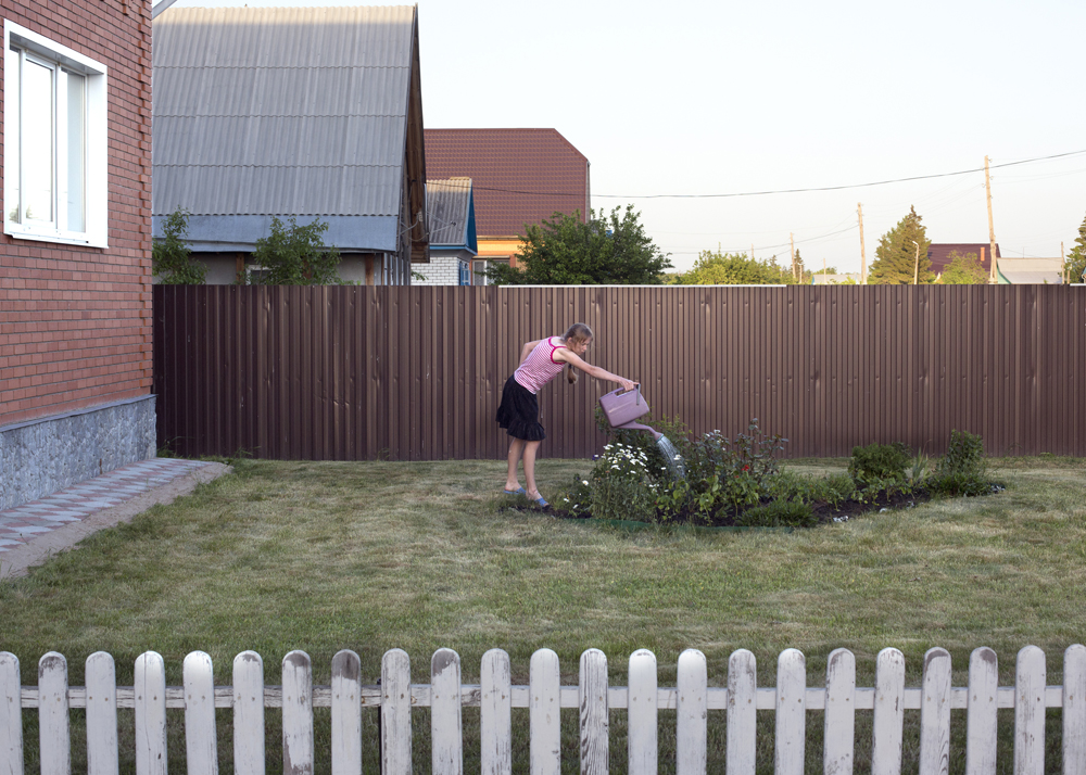 A girl waters plants in the front yard of a new house purchased by her parents three days ago in Solnzevka, Russia, 2014.