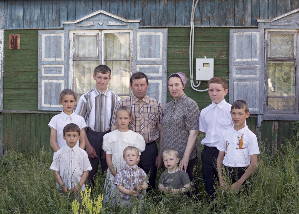 A family of ten stands in front of their old house, which will be demolished soon in Petrovka, Omsk Oblast, Russia, 2014.