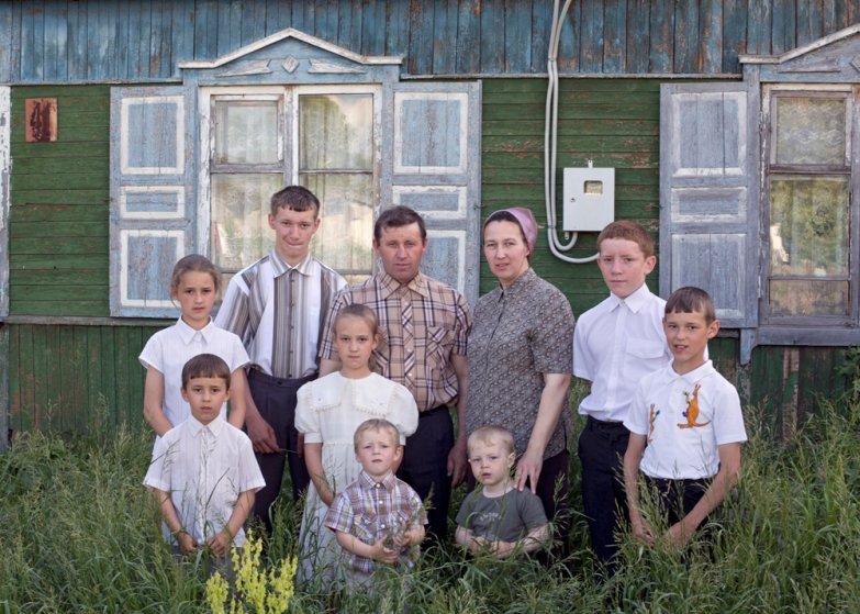 A family of ten stands in front of their old house, which will be ­demolished soon in Petrovka, Omsk Oblast, Russia, 2014.