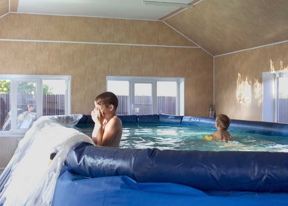 Young boys play in a swimming pool three days after a house purchase in Solnzevka, Russia, 2014.