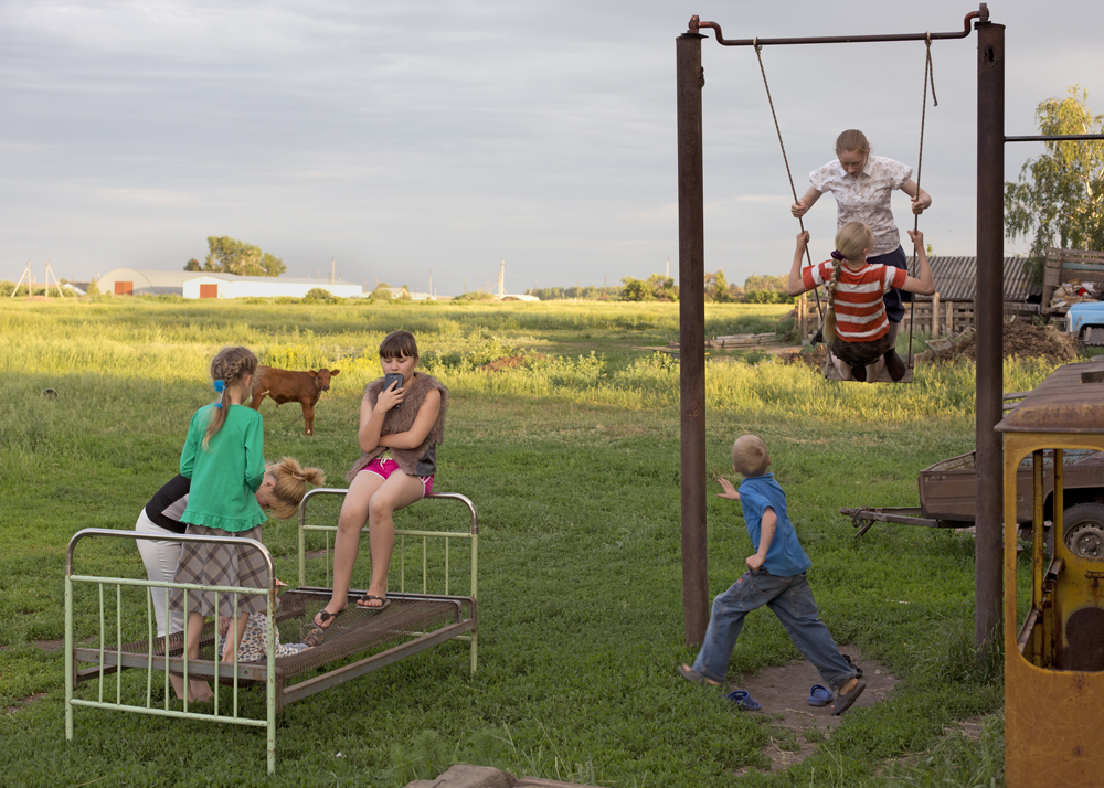 Siblings play with their Russian neighbors in the backyard in Pertrovka, Russia, 2014.