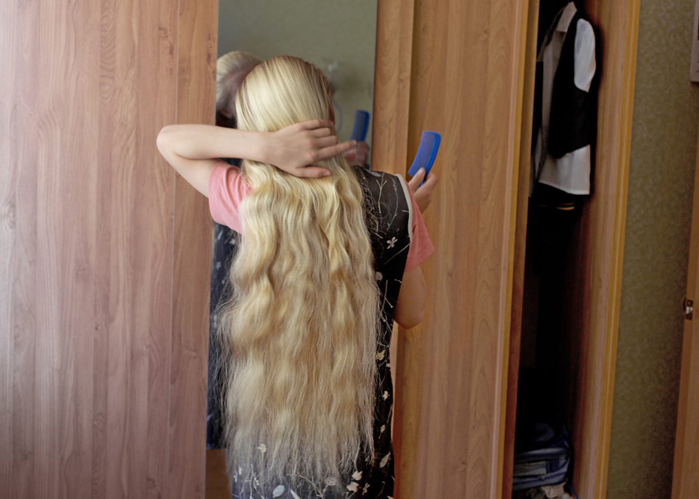 An 11-year-old girl braiding her hair before church service in Petrovka, Russia, 2014.