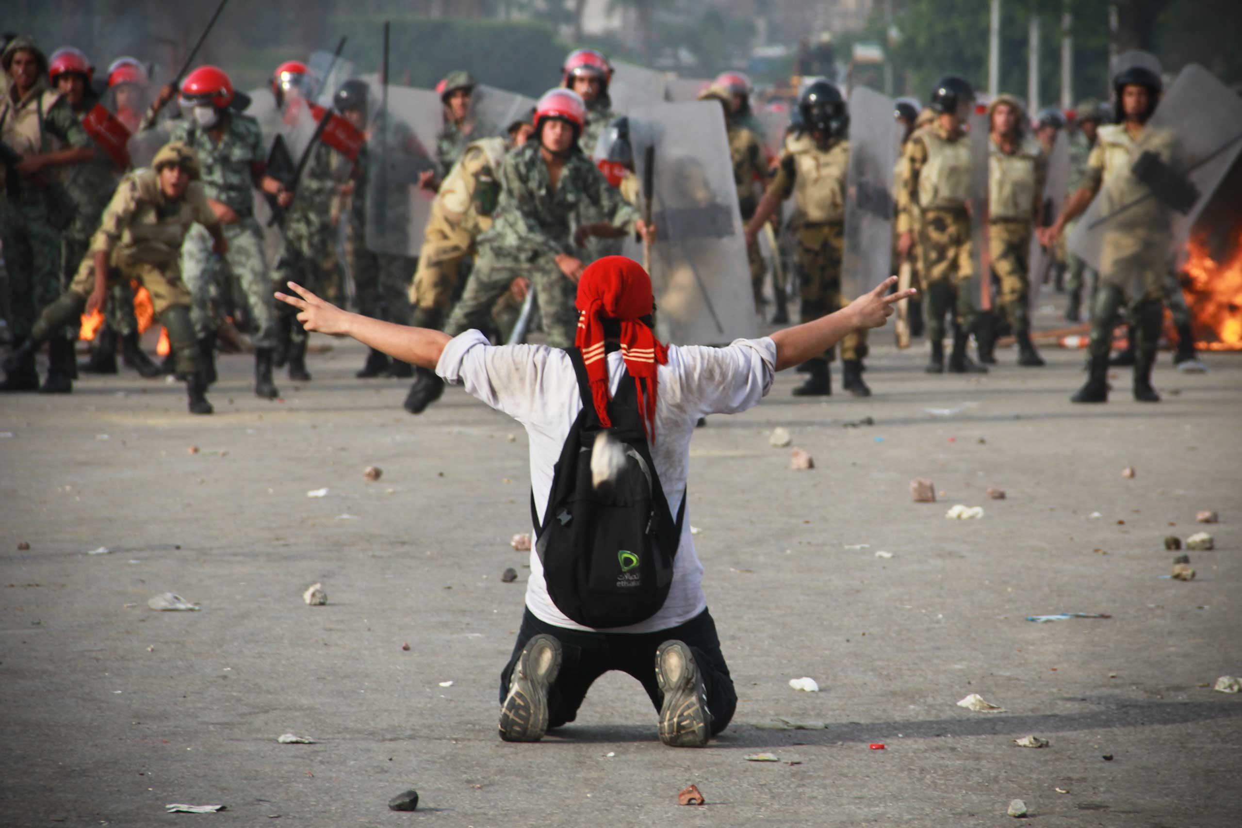 A protester raises his arms in defiance of security forces as projectiles and rubber bullets fly by during a clash in the Abassiya neighborhood of Cairo, Egypt, May 2012.