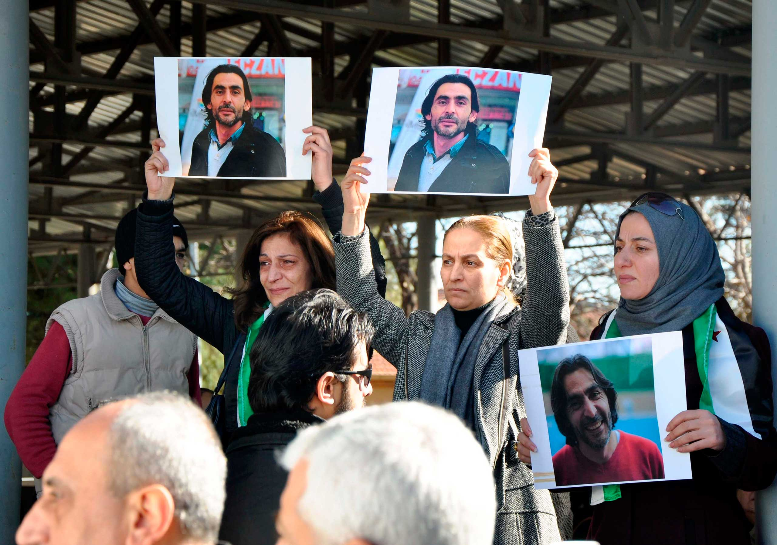 Women hold pictures of film maker Naji Jerf, a citizen journalist with the anti-ISIS activist group Raqqa is Being Slaughtered Silently, who was killed Dec. 27 in Gaziantep, Turkey, on Dec. 28, 2015.