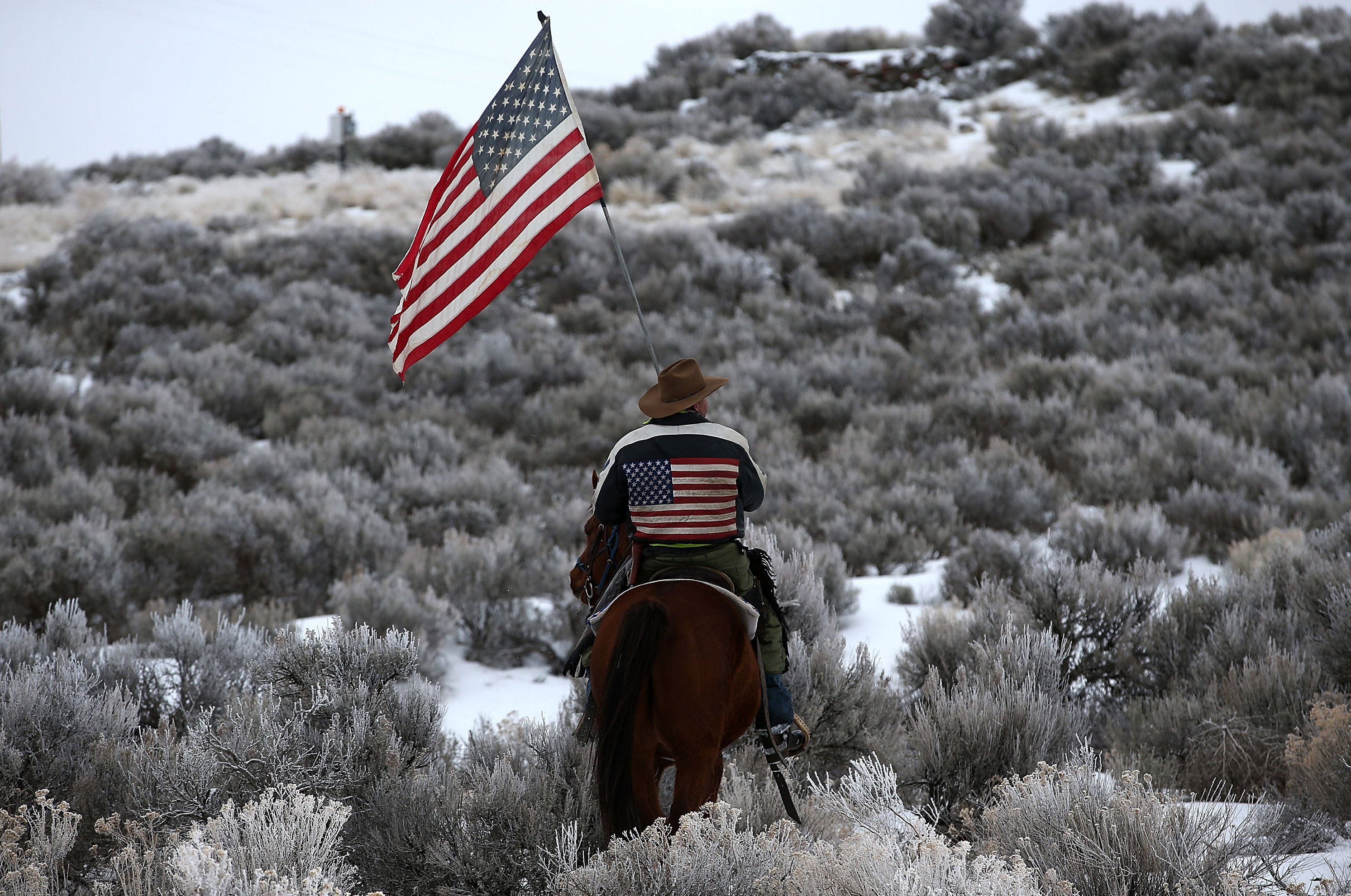 Dwayne Ehmer carries an American flag as he rides his horse on the Malheur National Wildlife Refuge near Burns, Ore., on Jan. 7, 2016.