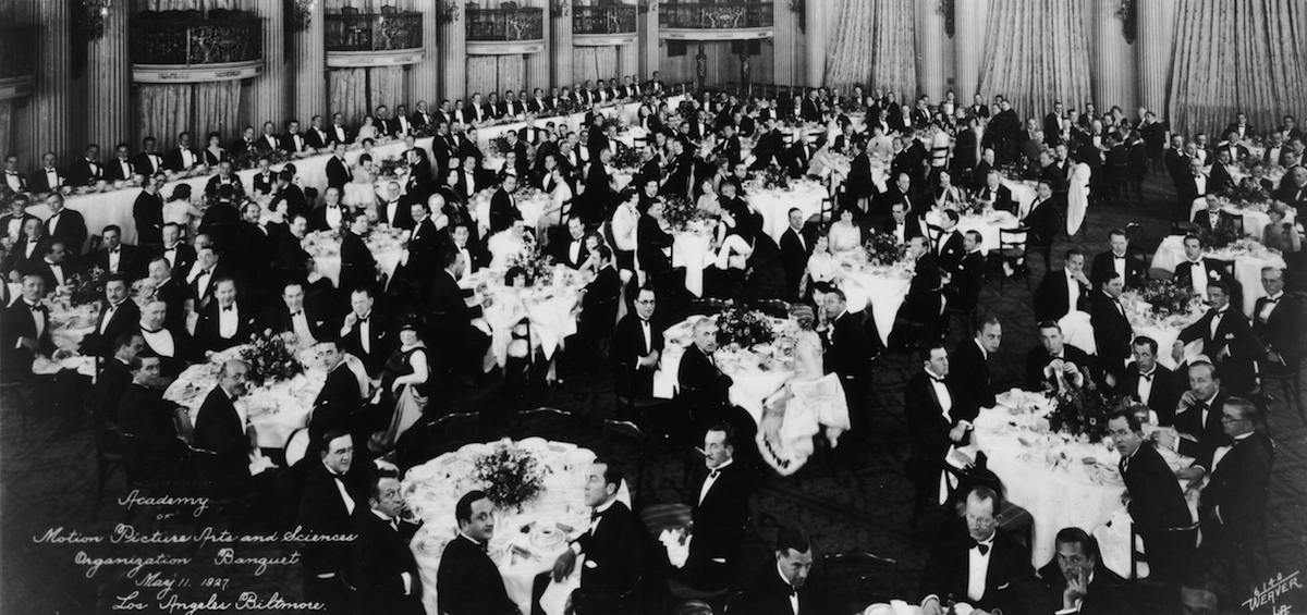 Interior view of formally dressed men and women seated at tables during the May 11, 1927, first organizational meeting of the Academy of Motion Picture Arts and Sciences in the Crystal Ballroom of the Los Angeles Biltmore Hotel.