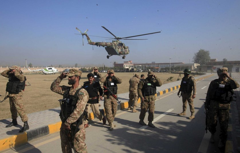 Soldiers holds their caps as a helicopter flies past during an operation, after a militant attack at Bacha Khan University in Charsadda, Pakistan, Jan. 20, 2016.
