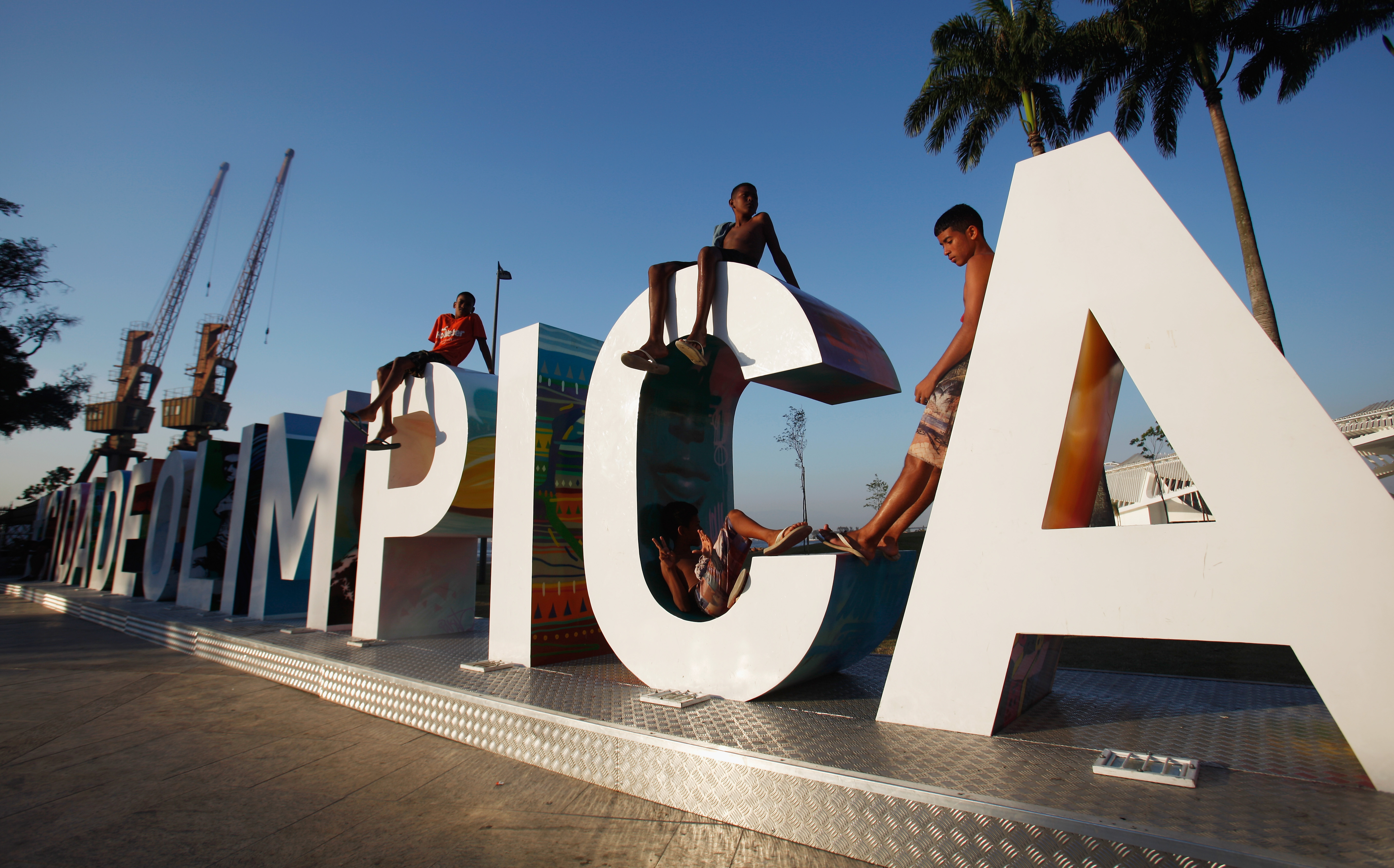 Teens sit on a new sign reading 'Cidade Olimpica' (Olympic City) in the historic port district in Rio de Janeiro, Brazil on Oct. 15, 2015.