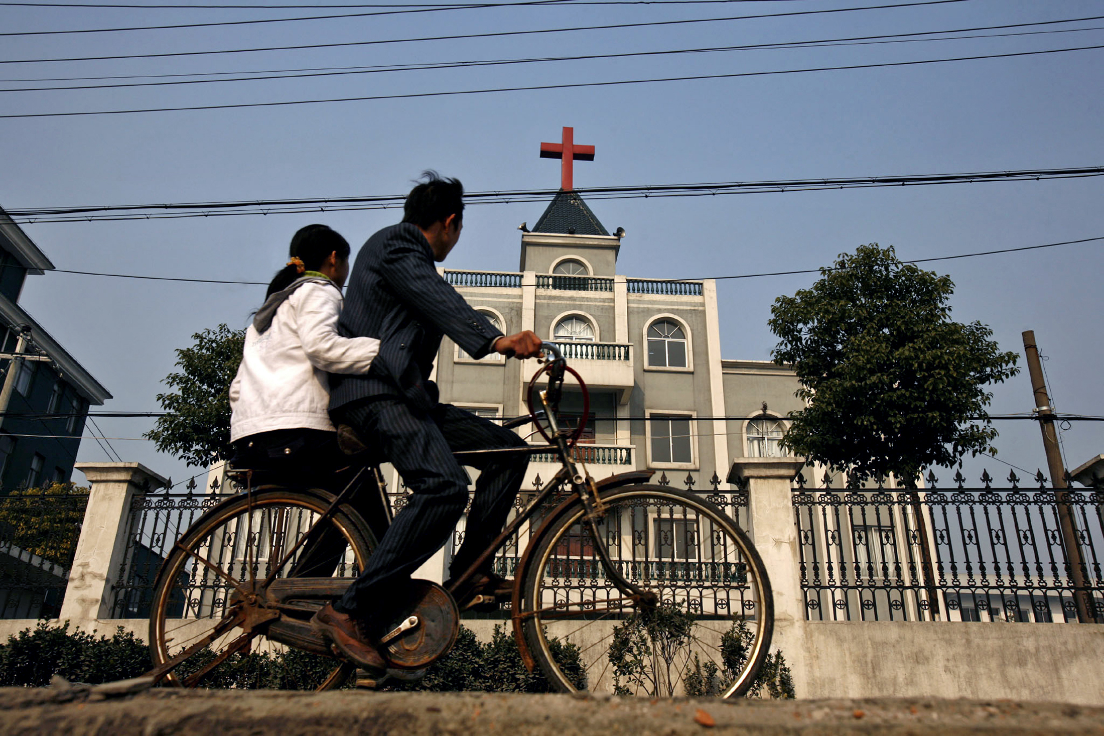 A local resident rides a bicycle past a church in Xiaoshan, a commercial suburb of Hangzhou, the capital of China's Zhejiang province, on Dec. 21, 2006