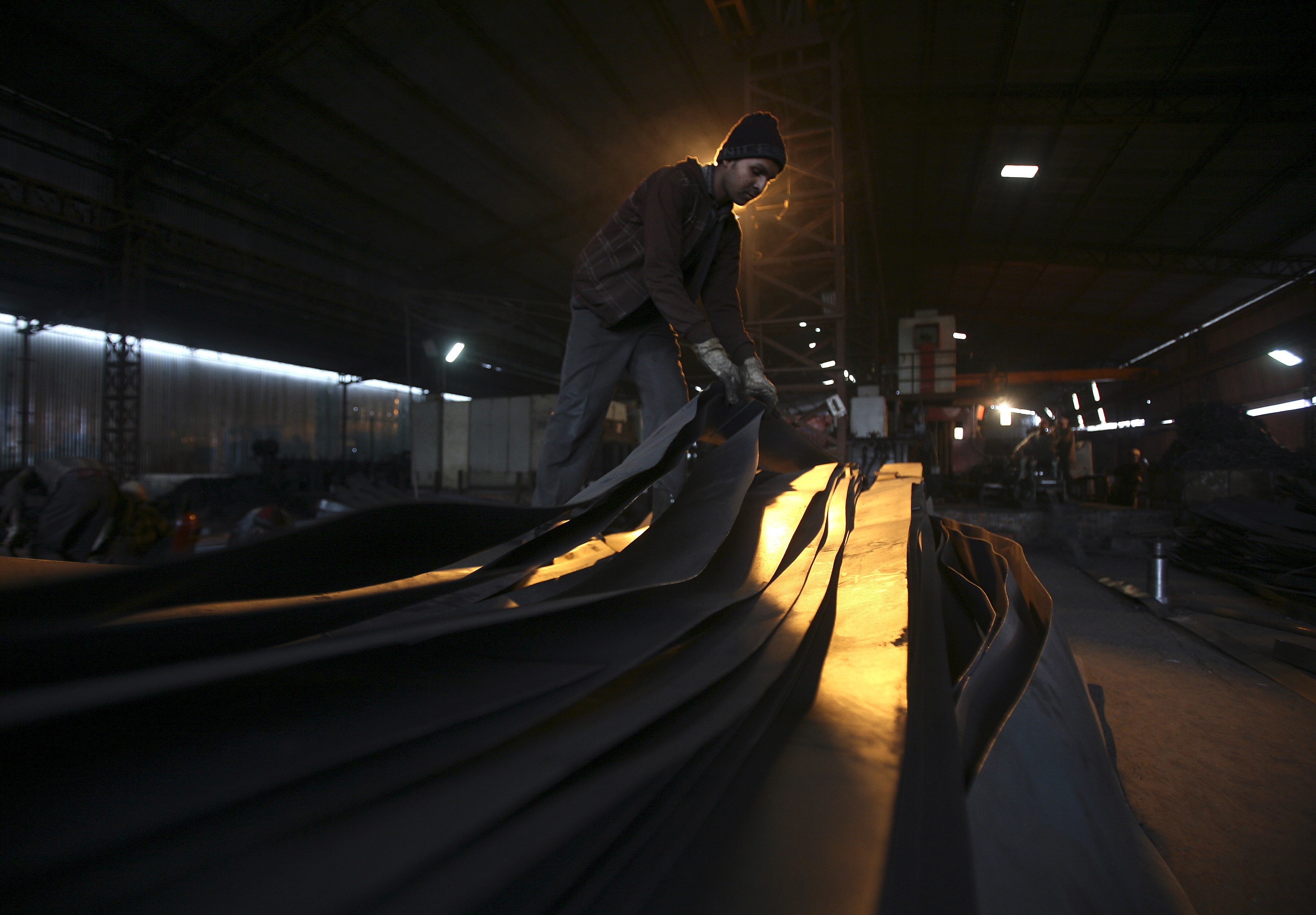 An employee works inside an iron factory on the outskirts of Jammu February 3, 2015.