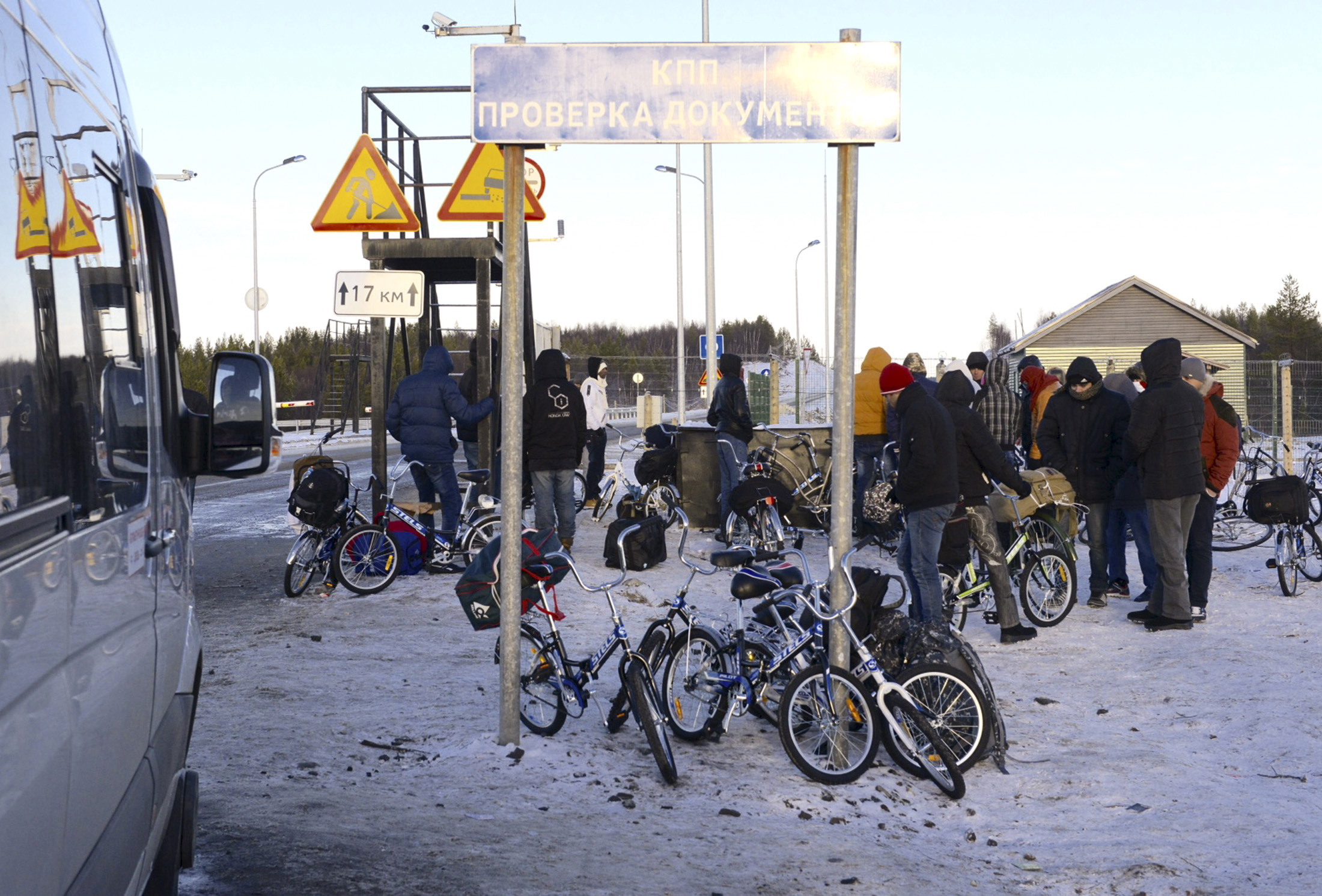 Refugees and migrants gather near a check point on the Russian-Norwegian border outside Nickel (Nikel) settlement in Murmansk region, Russia, on Oct. 30, 2015