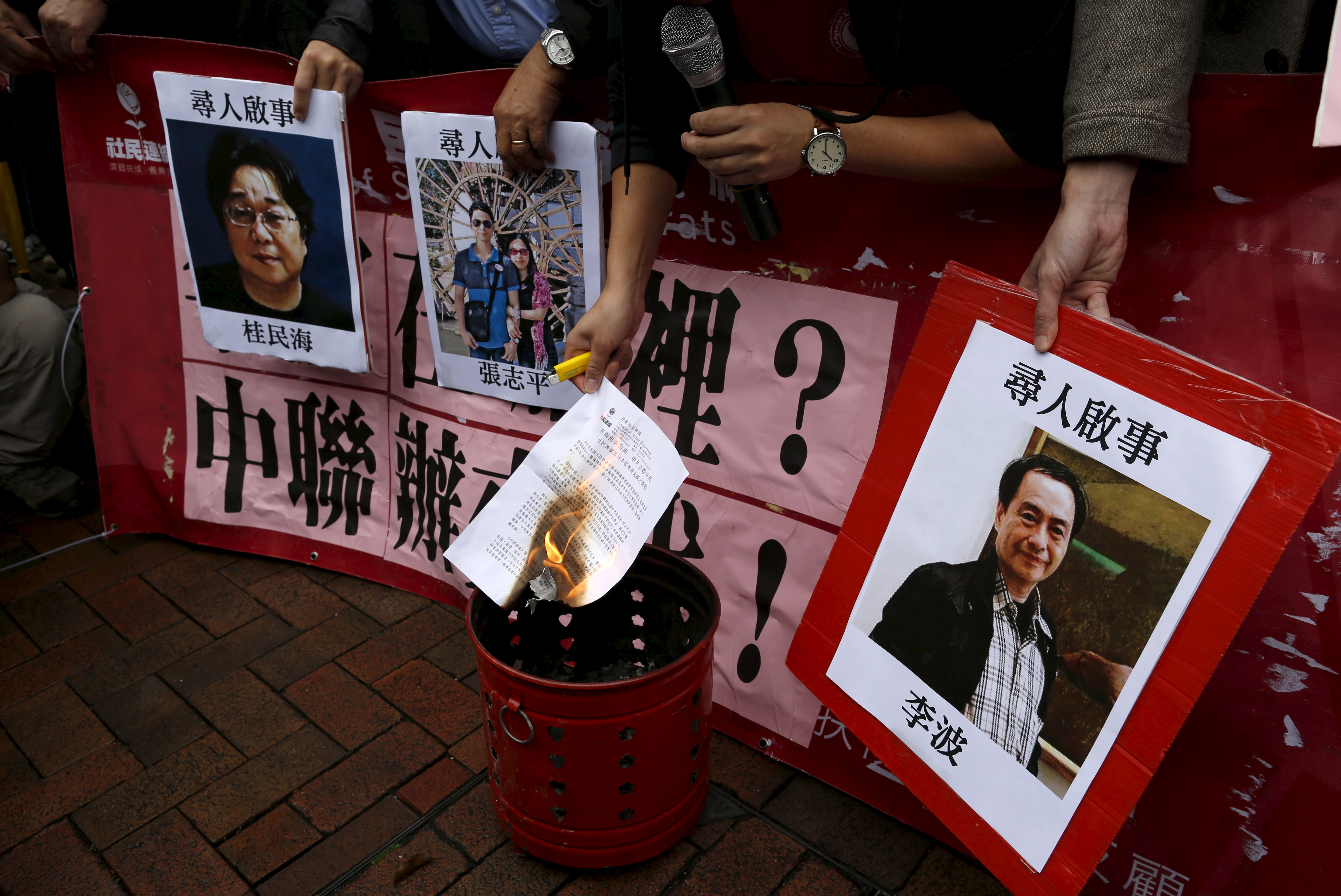 A pro-democracy demonstrator burns a letter next to pictures of missing staff members of a publishing house and a bookstore, including Gui Minhai, a China-born Swedish national who is the owner of Mighty Current,  Cheung Jiping, the business manager of the publishing house and Causeway Bay Books shareholder Lee Bo (L-R), during a protest to call for an investigation behind their disappearance, outside the Chinese liaison office in Hong Kong, China January 3, 2016. Hong Kong opposition lawmakers protested on Sunday outside Beijing's representative office in the Chinese-ruled city over the disappearance of a bookseller who specializes in publications critical of the Communist Party government. REUTERS/Tyrone Siu - RTX20UEE