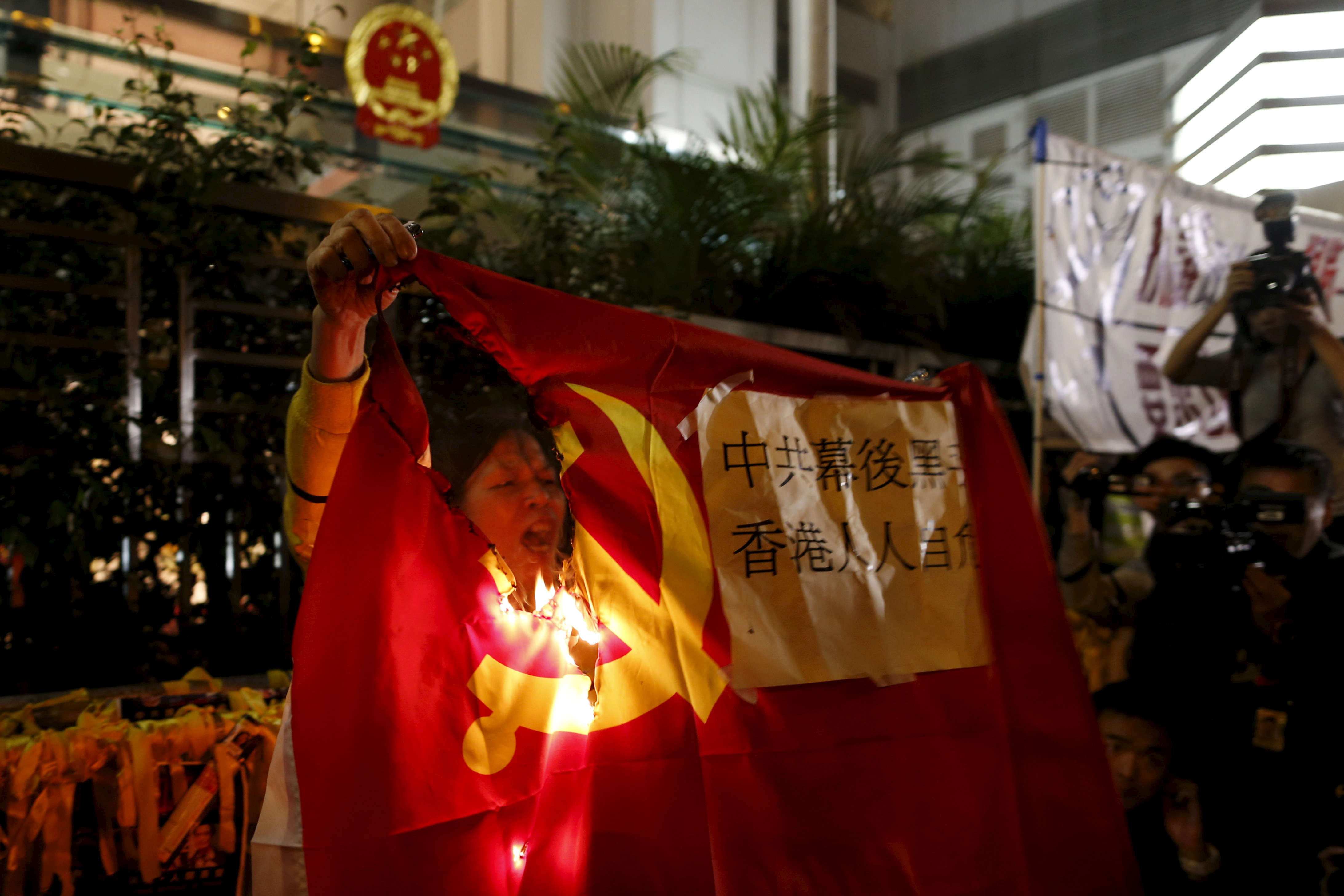 A demonstrator burns a flag of the Chinese Communist Party during a protest over the disappearance of booksellers, outside the Chinese Liaison Office in Hong Kong on Jan. 10, 2016