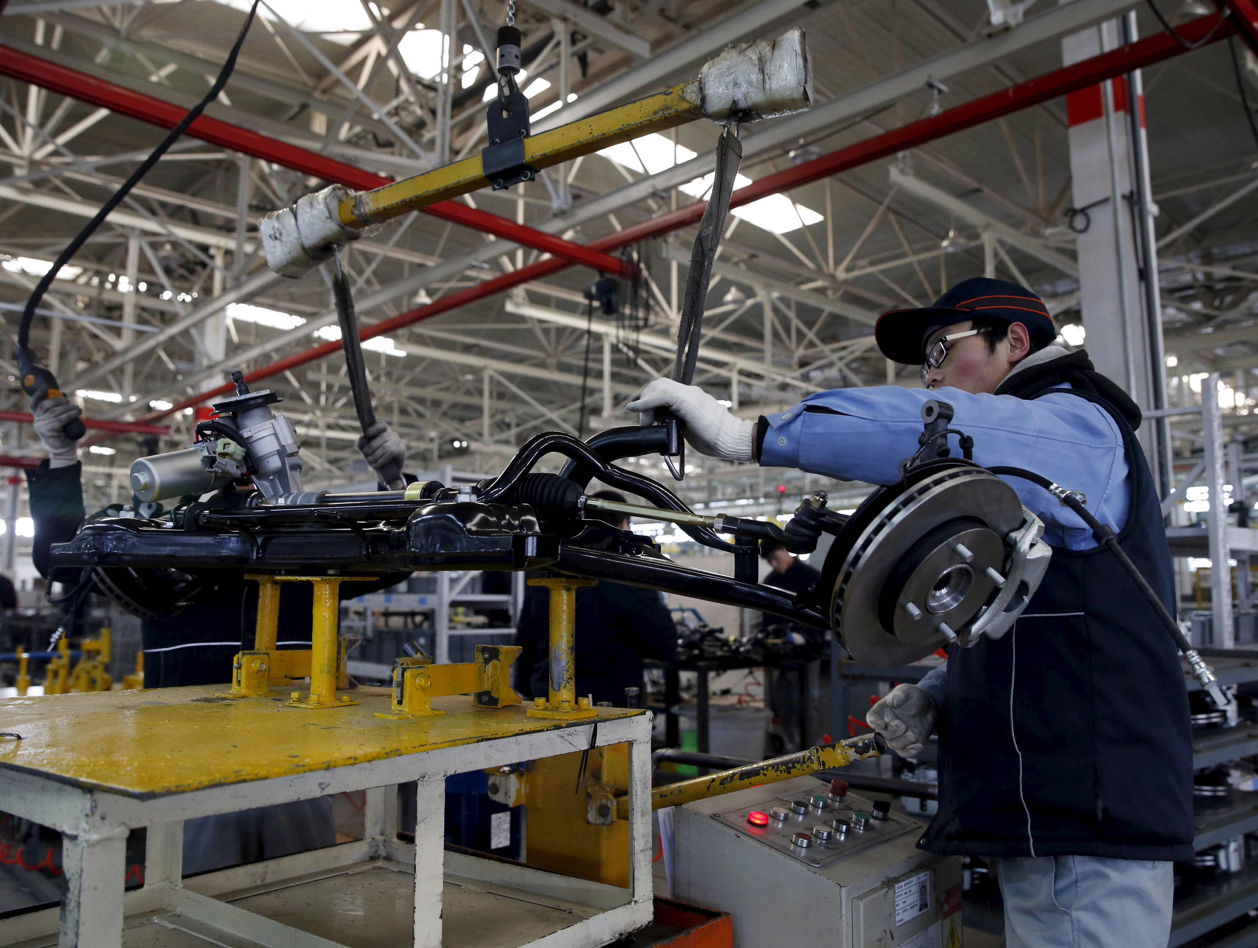 An employee works on an assembly line producing electronic cars at a factory of Beijing Electric Vehicle, funded by BAIC Group, in Beijing, China, Jan. 18, 2016.