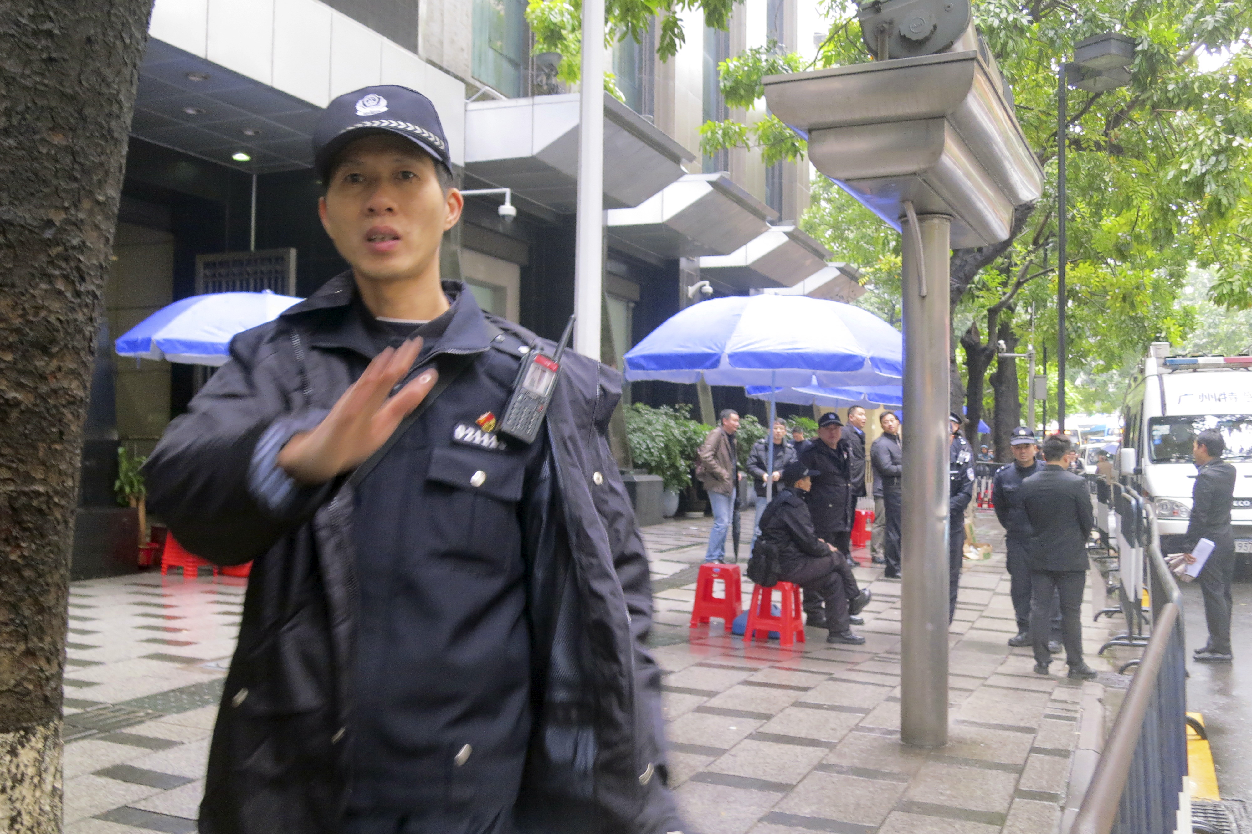 Policemen stand guard outside a court in the southern Chinese city of Guangzhou Jan. 29, 2016. A court in Guangzhou on Friday jailed three men on subversion charges