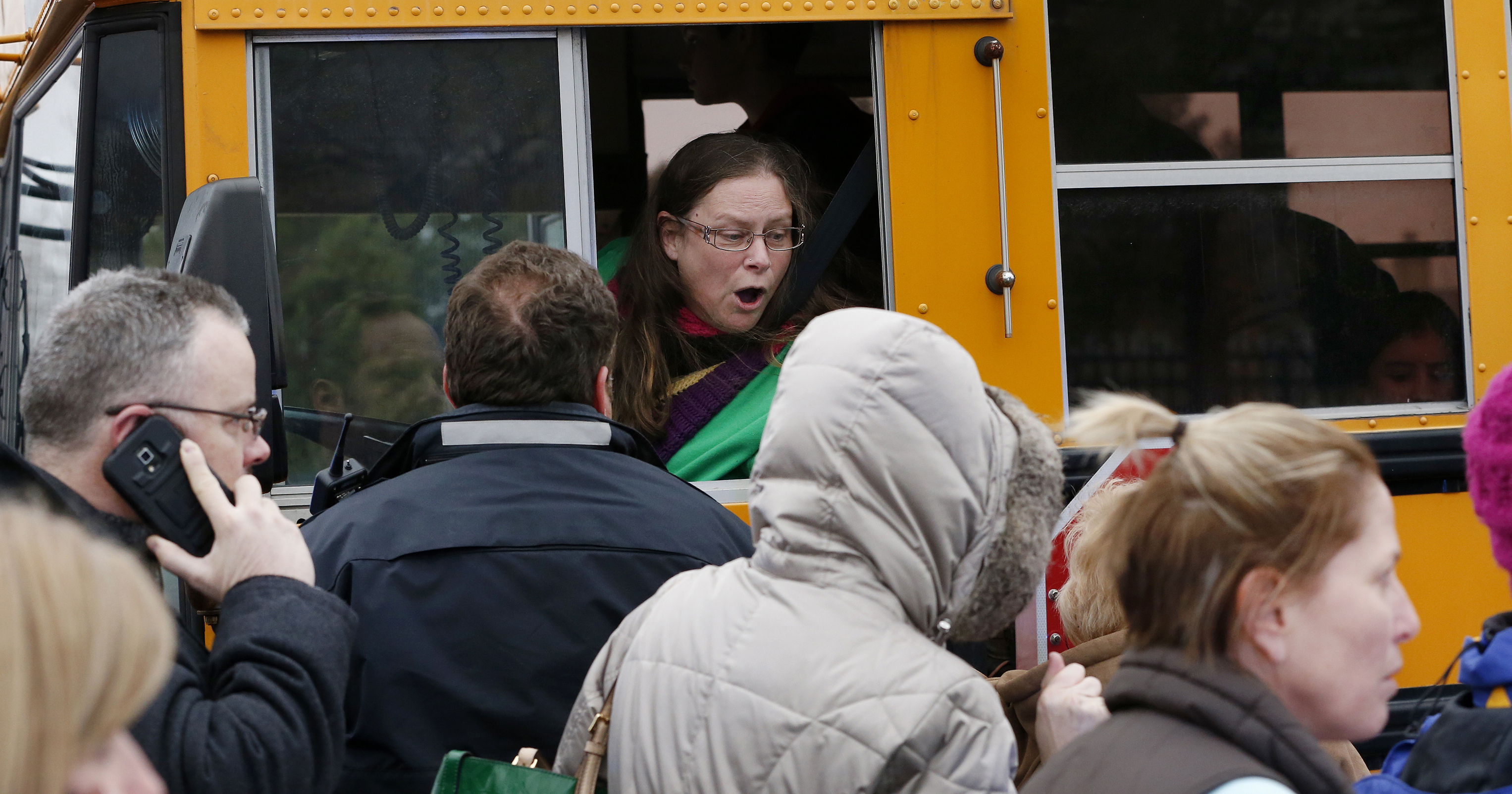 A school bus driver yells to a parent that their child is safe after a bus accident at Amy Beverland Elementary School that left several students injured and one adult dead on school grounds on Jan. 26, 2016 in Indianapolis, Ind.