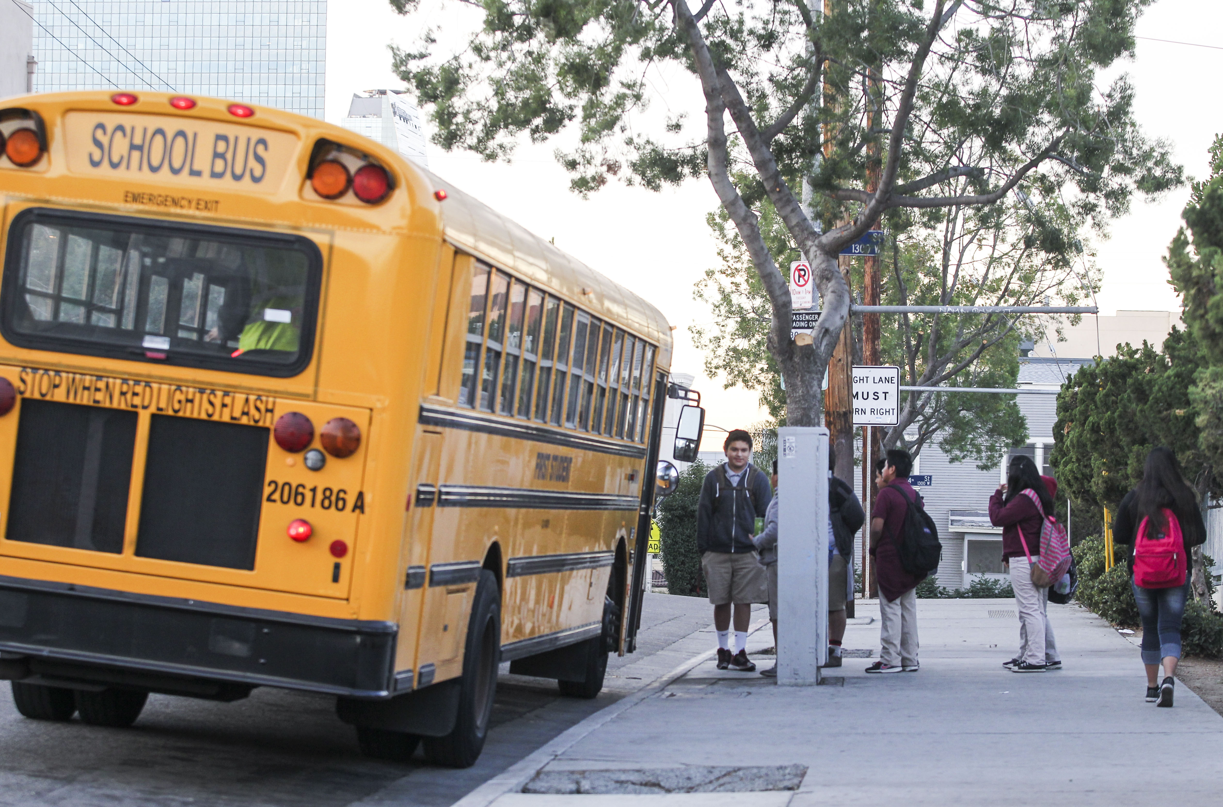 Students line up for a school bus outside a school in Los Angeles on December 16, 2015.