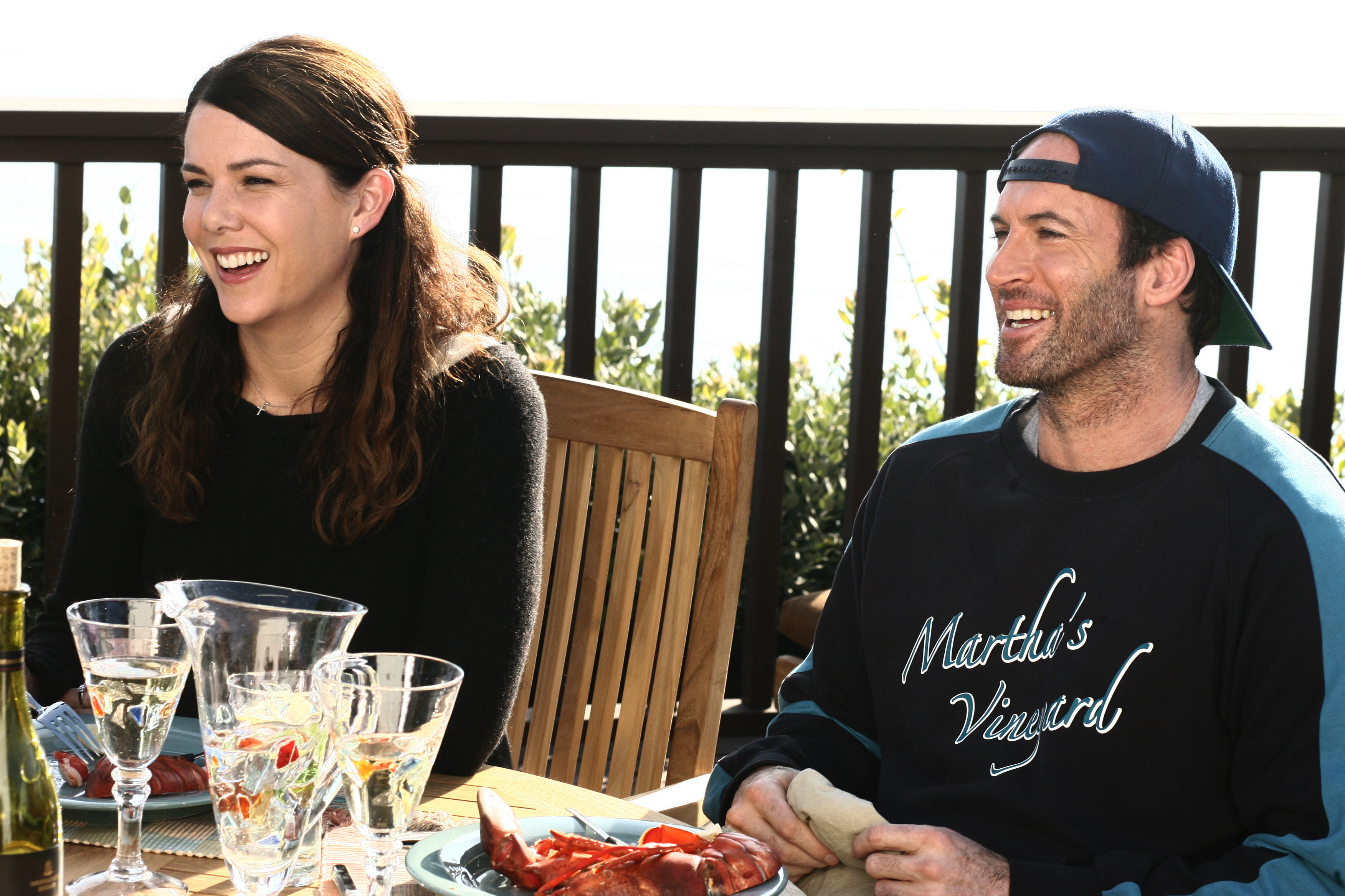 Medium shot of Lauren Graham as Lorelai sitting at patio dining table with Scott Patterson as Luke.