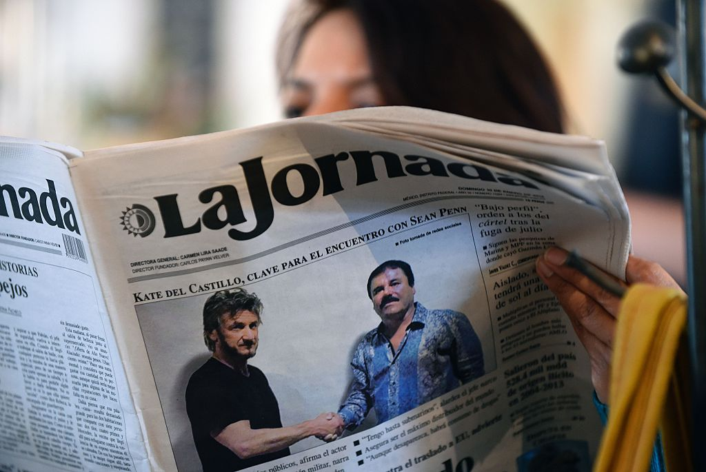 A woman reads La Jornada newspaper in Mexico City on Jan. 10, 2016, which shows a picture of drug lord Joaquin Guzman, aka  El Chapo  (R), shaking hands with Sean Penn.