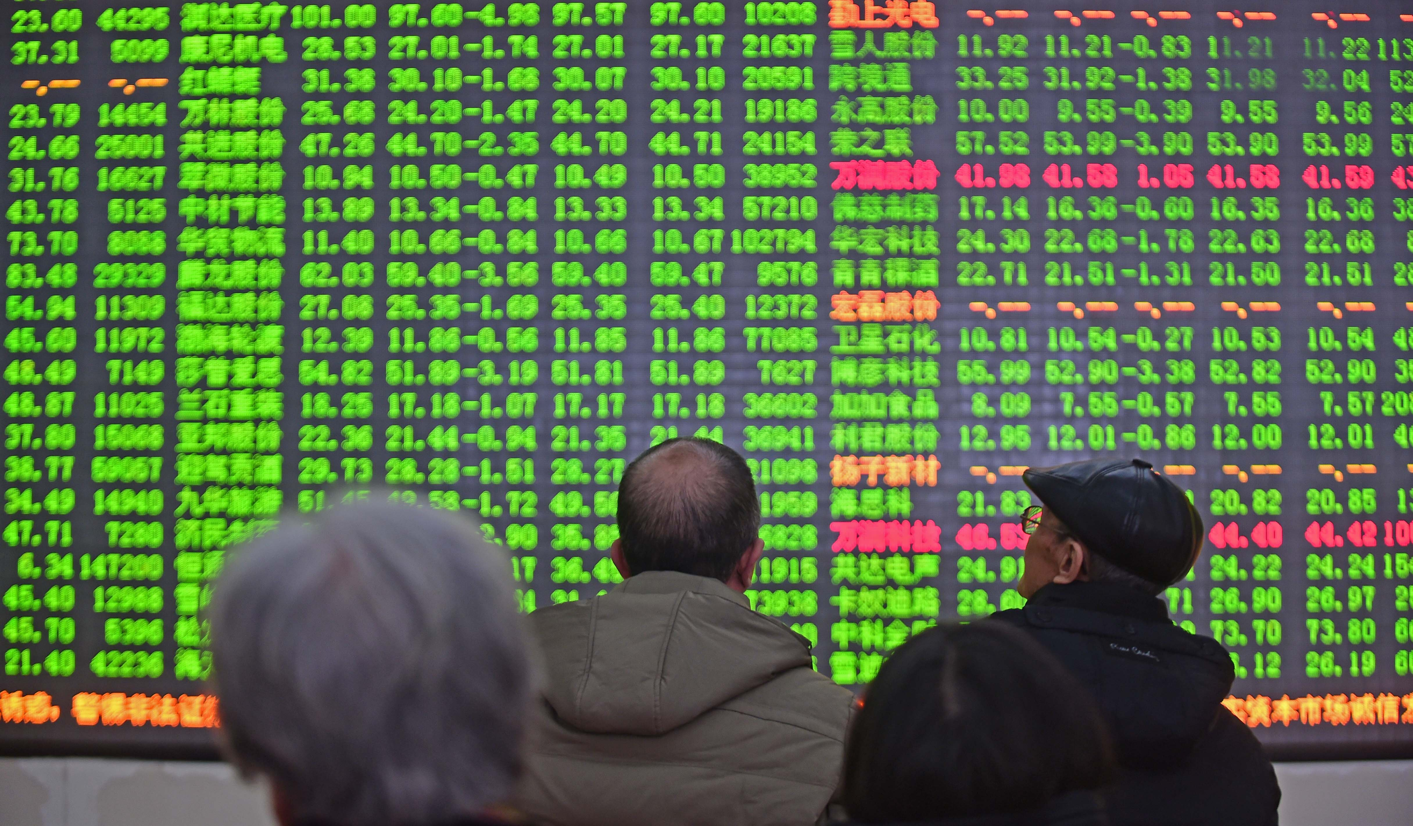 Investors look through stock information at a trading hall in Shenyang, China on Jan. 4, 2016.